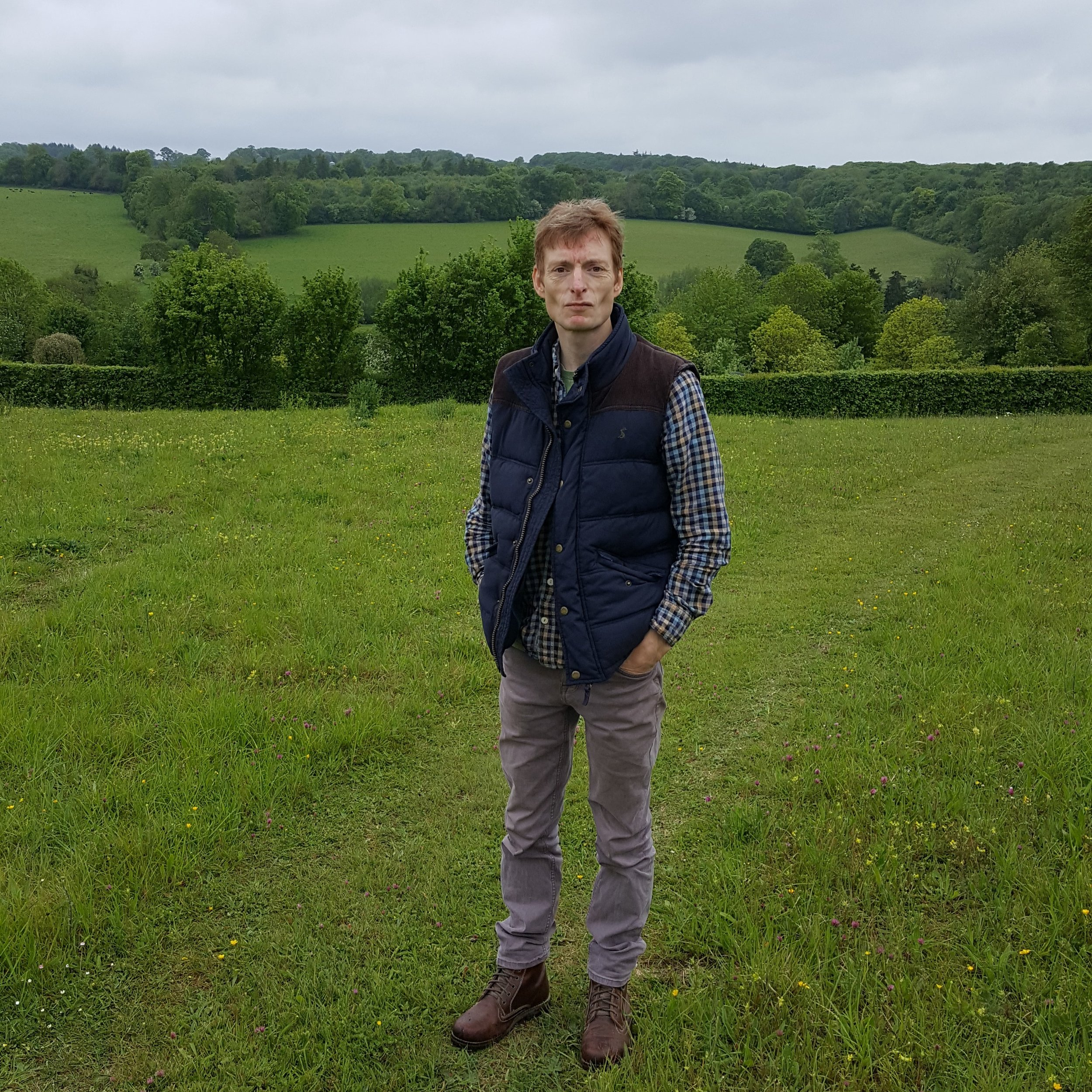 Matt in front of the wild flower meadow and view enjoyed by his bees