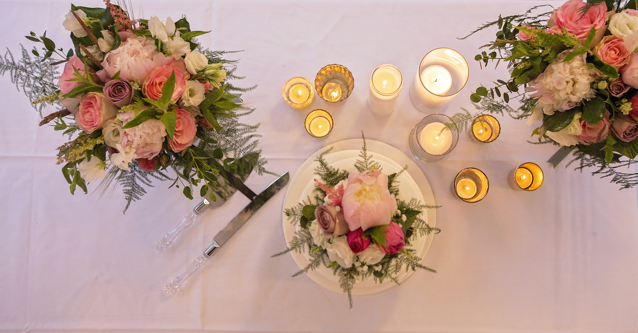 Beautiful shot of the cake table decorated with bridal bouquets.