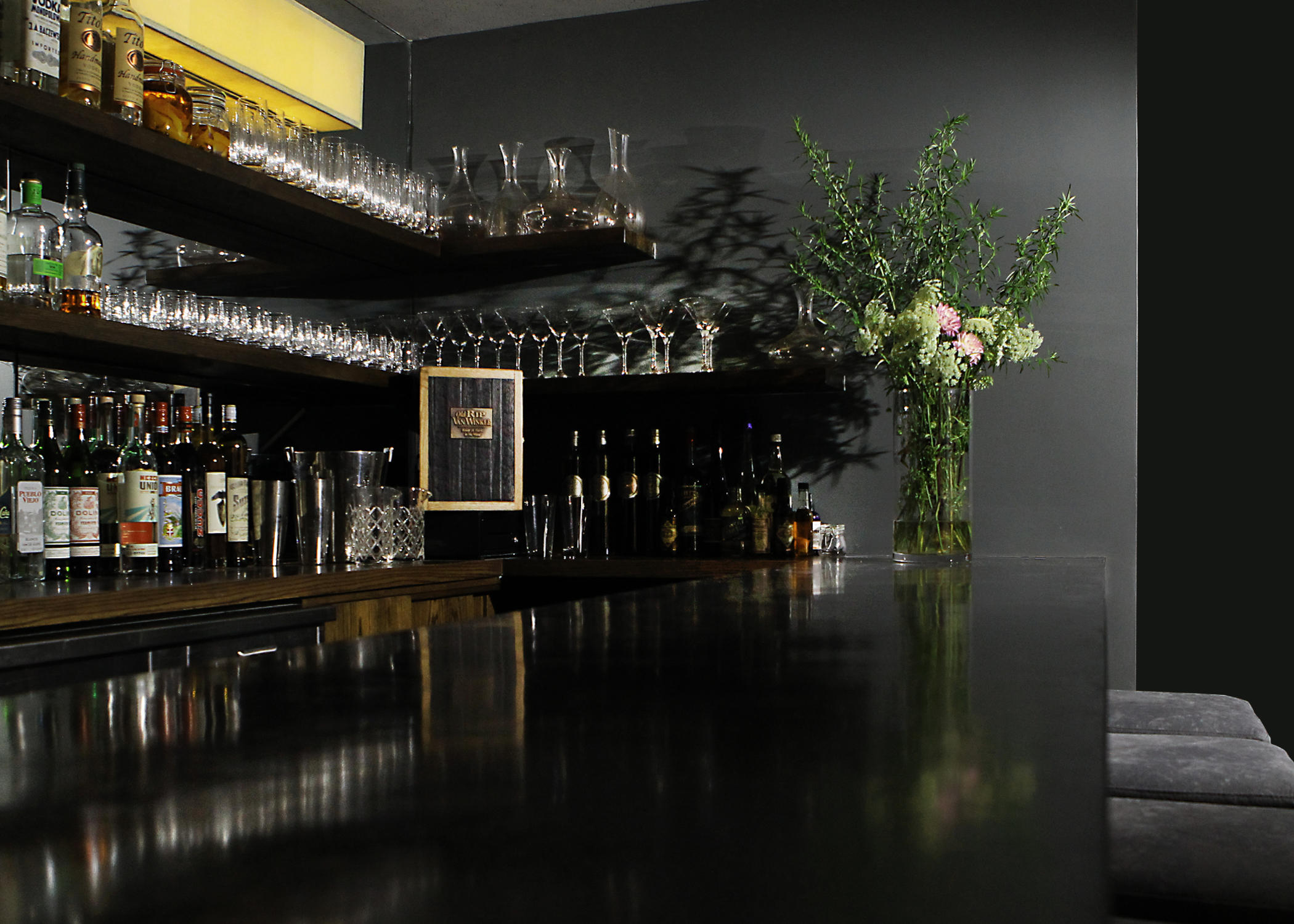 The front bar features a new custom poured black concrete bar top, with wrap-around floating oak shelving behind and John Wigmore custom light-fittings on a mirrored backdrop.