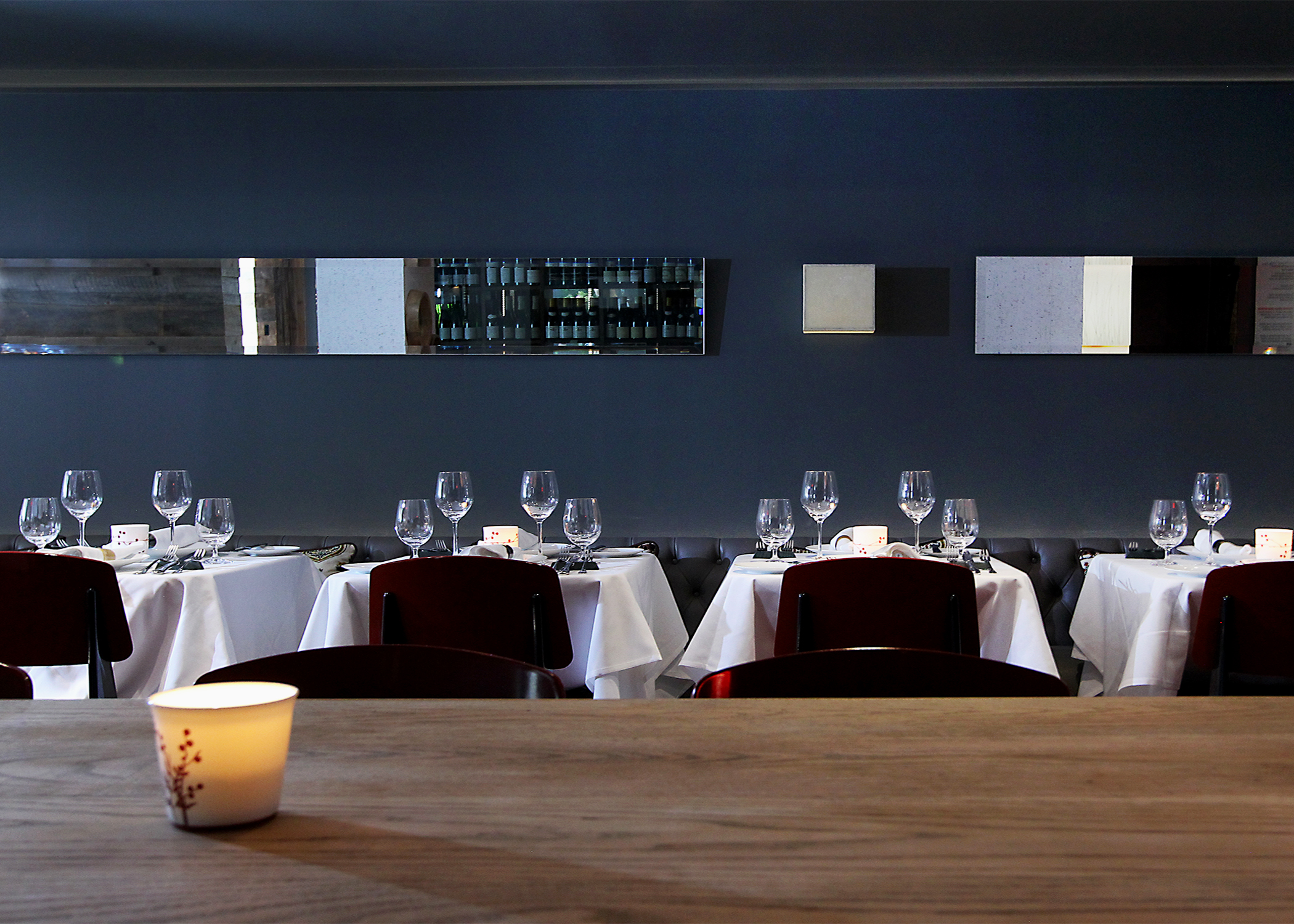 The main dining space was refreshed with a central floating oak farm table, cork wall/ceiling linings and carefully located lighting, mirrors and artwork for an elevated fine dining experience.
