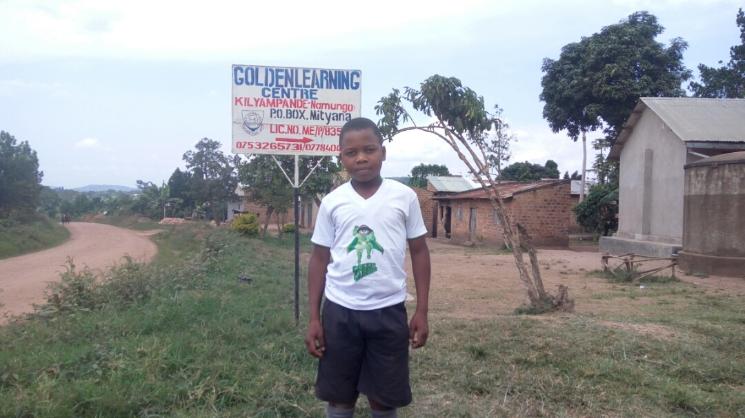 A Student Champion proudly wearing his t-shirt at Golden Learning Centre in Mityana