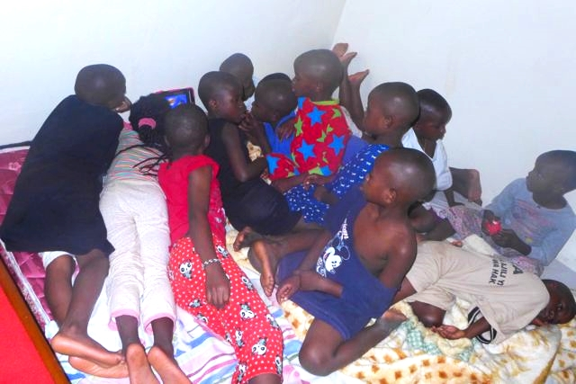 "13 children having been bathed and in ""pajamas"" (Madel's t-shirts) watching cartoons before bed."