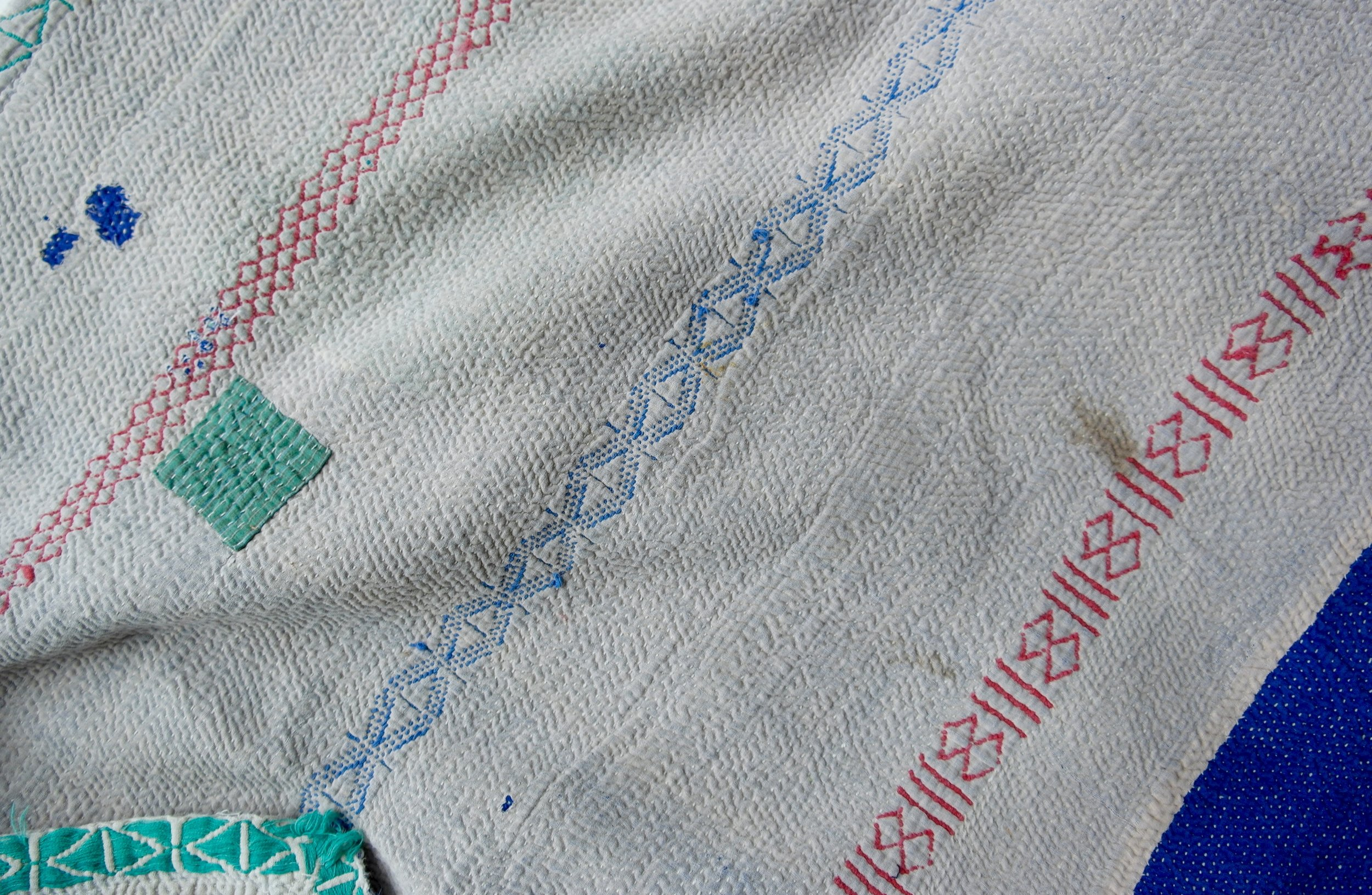 Kantha quilt with some staining, a sewn-on patch and a peeling spot