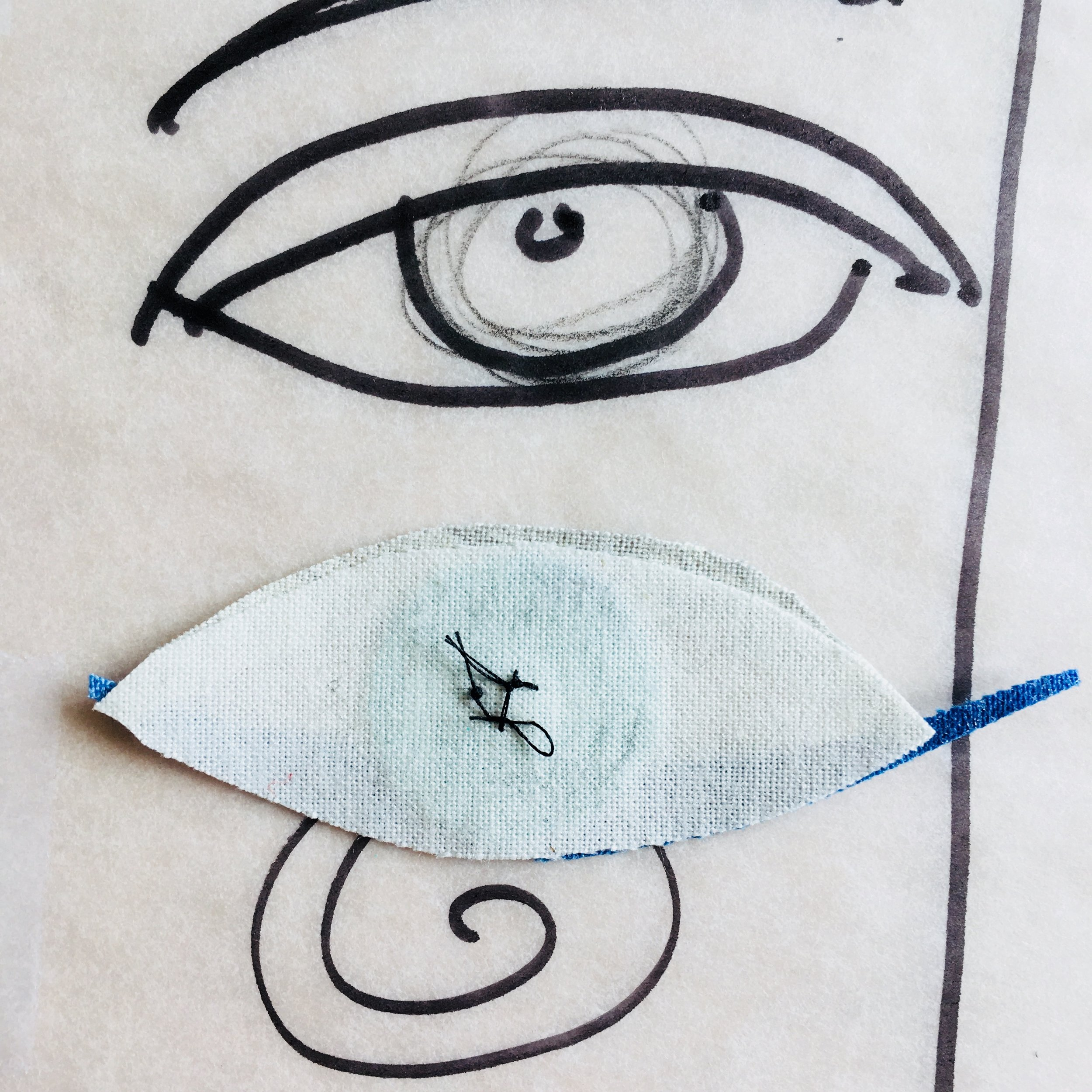 Before I go further I like to fuse the eyeball so I don't lose the little pieces. Then I do a couple of hand stitches in the pupil.
