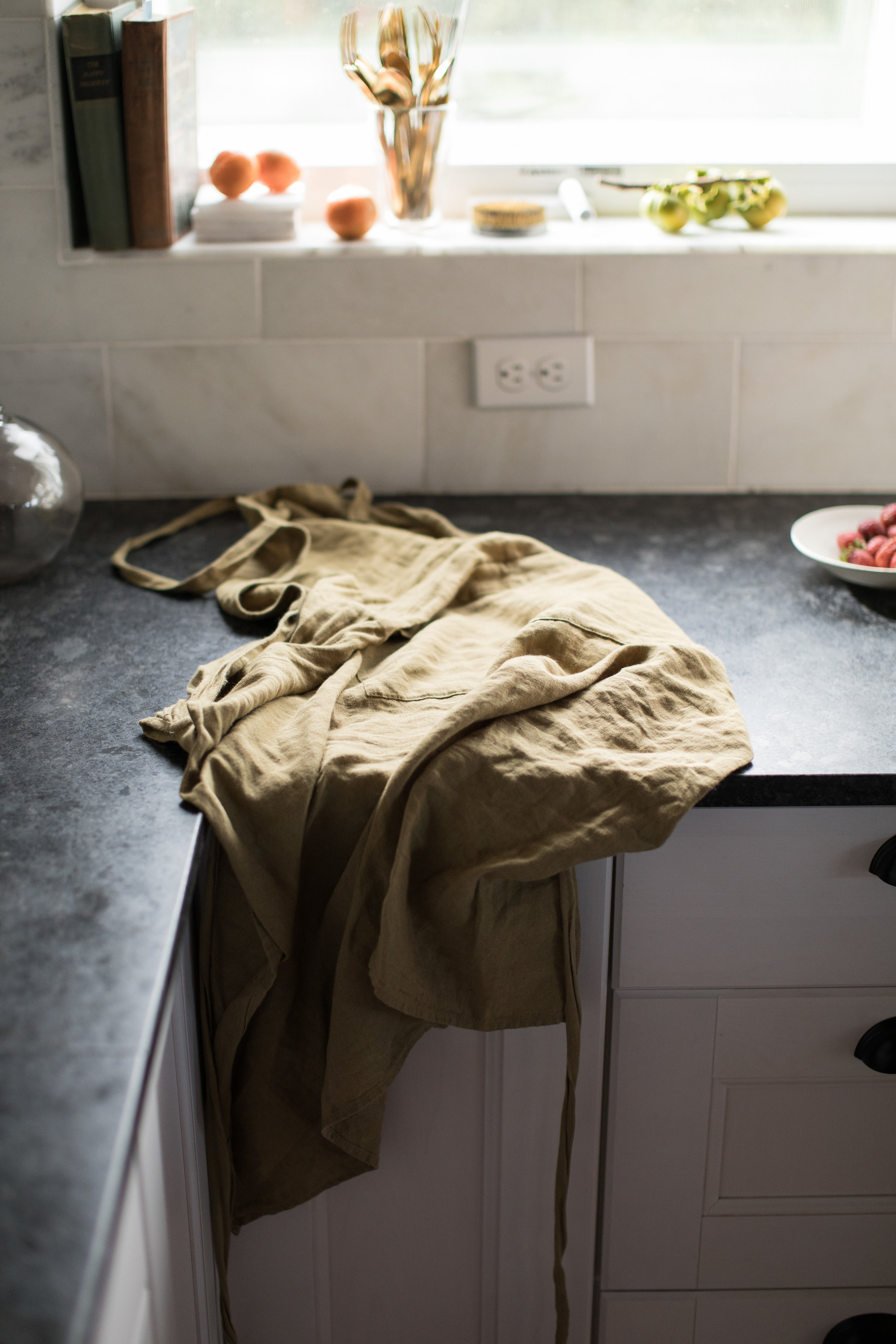 Source: Linen Apron, Gold Flatware, Ceramic Dish on counter