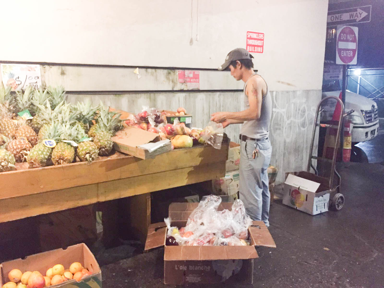 Man repacking fruits to be sold at a cheaper price and in bulk