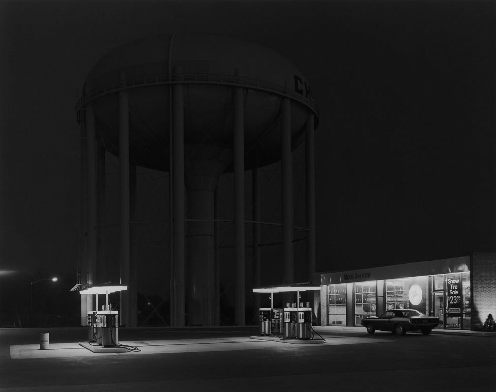 "George Tice, ""Petit's Mobil Station, Cherry Hill, NJ, 1974."" Tice's best-known image was a 2-minute exposure on 8x10 film that took 10 minutes to expose because the photographer had to repeatedly cover his lens due to cars passing through the scene."