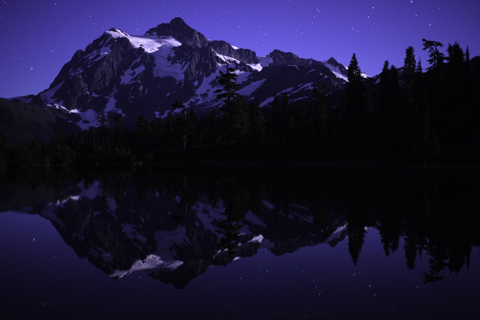 Mount Shuksan in North Cascades National Park sits reflected under a starry summer sky. © 2016 Chris Nicholson.