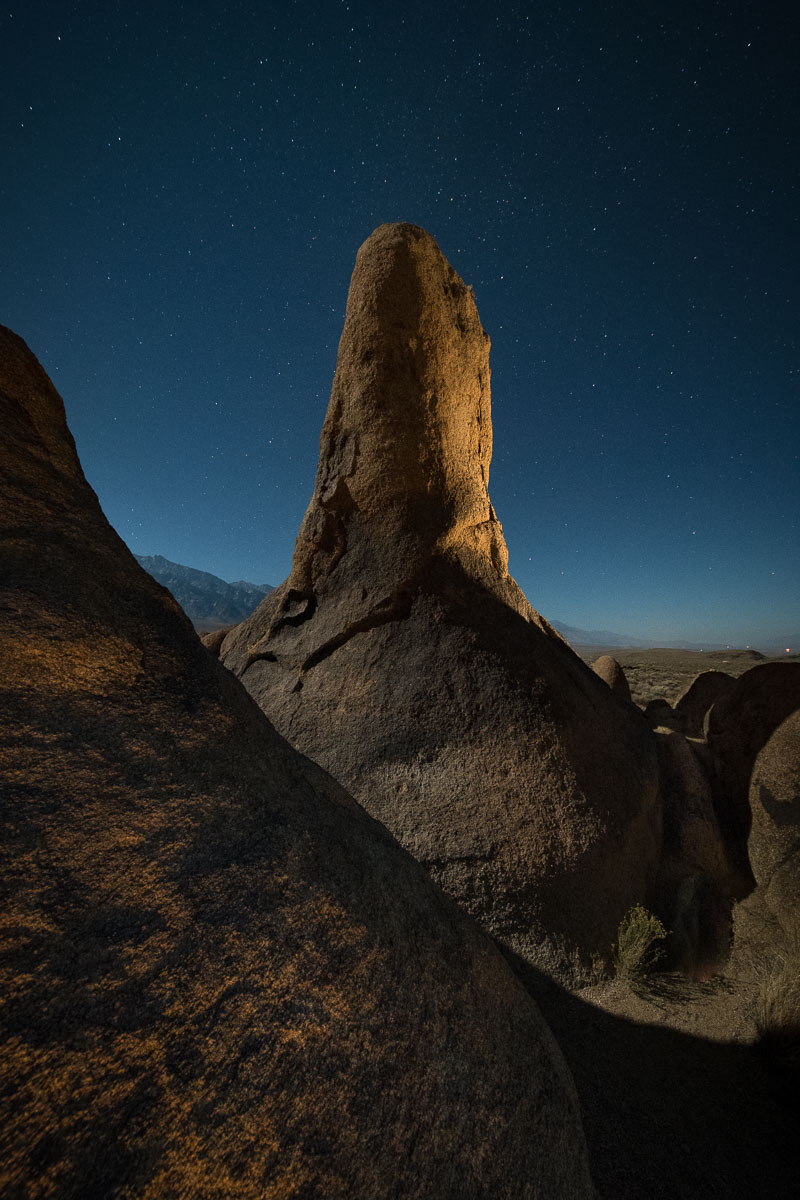 Lady Boot Arch from behind, Alabama Hills,  Eastern Sierra , California. Lighting with a warm-gelled  Coast HP5R  flashlight from camera right, low and just in front, plus behind and to the right of the rock column. Single shot. It took about eight tries to get the lighting right.  Nikon D850 ,  Irix 11mm f/4 Blackstone lens . 15 seconds, f/5.6, ISO 3200.