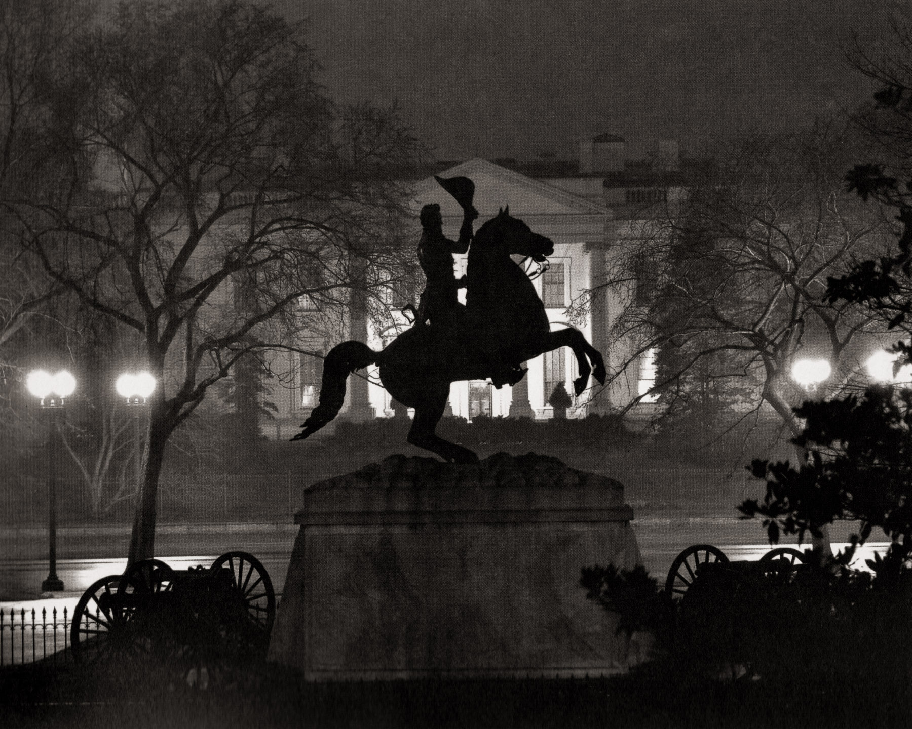 """Lafayette Square."" A silhouetted sculpture of Andrew Jackson on a rearing horse opposite the North Portico of the White House. Wentzel used an exposure that kept the sculpture in shadow, but preserved the detail of the illuminated White House. As was typical of this series, Wentzel chose to photograph on a wet and foggy night, a strategy that he no doubt observed in the night work of Brassai, and perhaps in Stieglitz's as well."