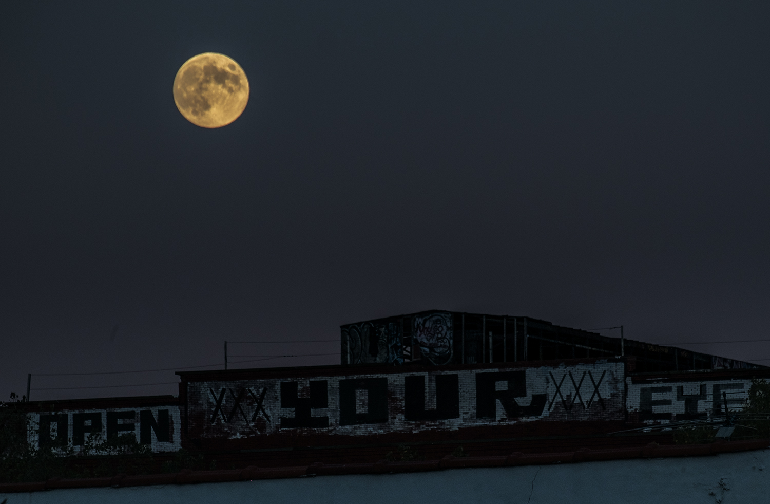 I was able to just eke out this shot of the full moon and get some detail in the buildings during nautical twilight. Fuji X-Pro1 with a  Fuji 55-200mm f/3.5-4.8  lens set at 200mm. 1/250, f/8, ISO 400.