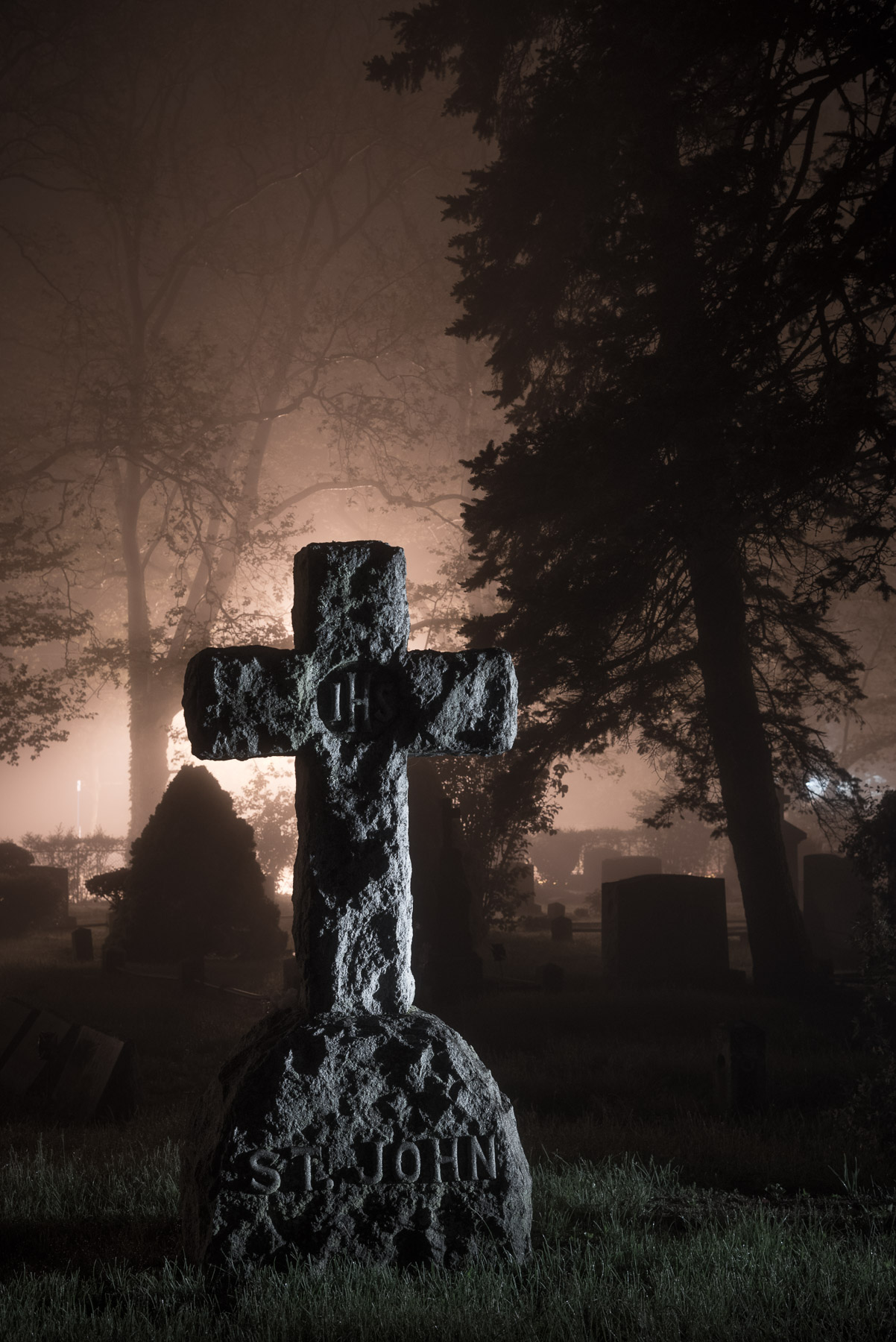 The warm-toned image is dominated by light from fog-diffused high pressure sodium vapor streetlights, with a key light on the cross from a Coast HP5R flashlight to camera right. Note that the 90-degree sidelighting exaggerates the texture in the cross, creating strong contrast in an otherwise soft scene. Nikon D750, Nikon 24-120mm f/4 lens at 50mm. 10 seconds, f/5.6, ISO 1600.