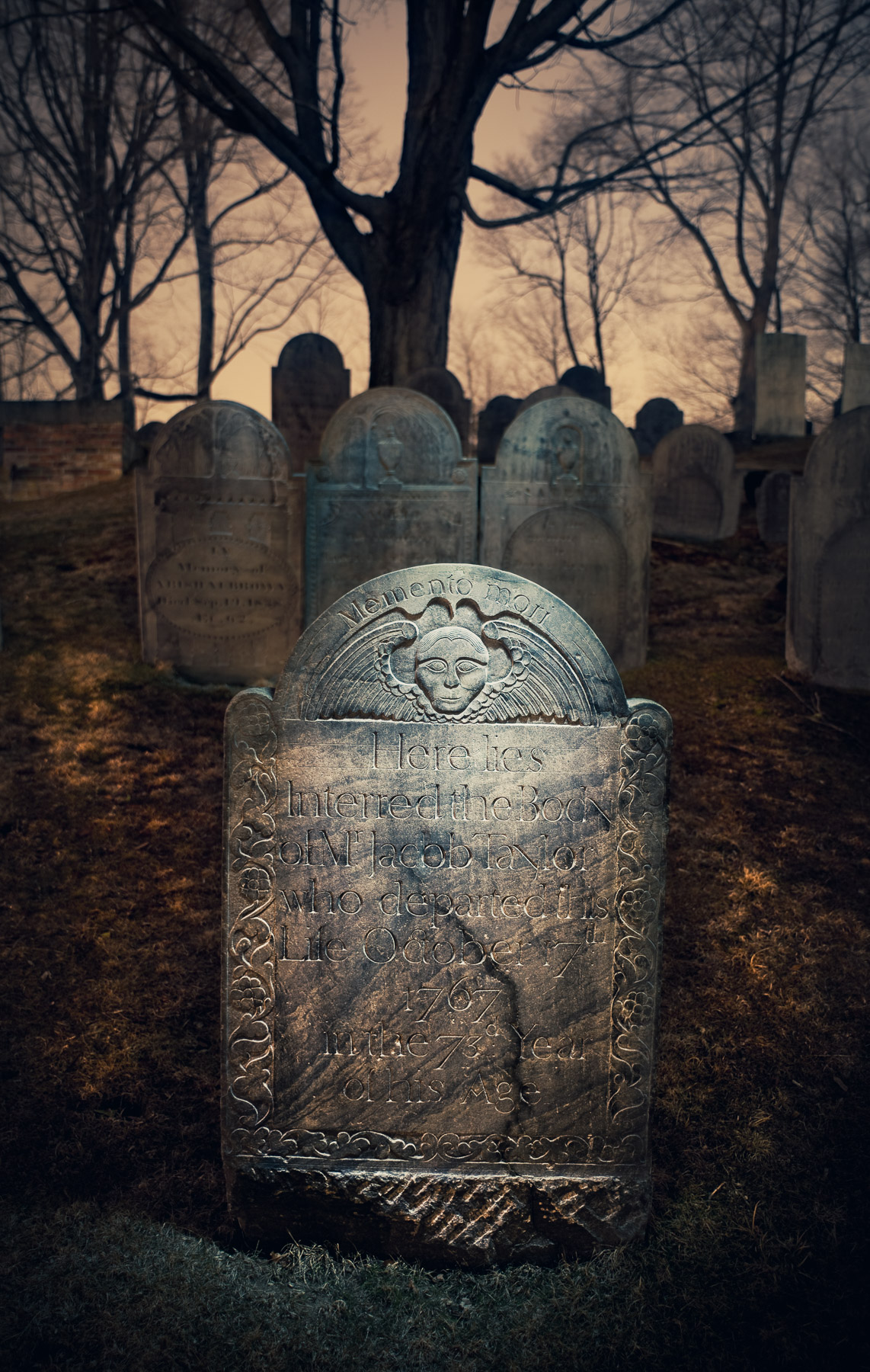 Jacob Taylor has resided at Sleepy Hollow in Concord, Massachusetts, since 1767. The image was made in 2010 with a Surefire G2 flashlight from slightly above the stone, flagged with black mat board so the camera didn't see the light. The three headstones in the middleground were lit with the same light source, but indirectly. I bounced the light off of a  12-inch Wescott reflector  from behind the central stone. The shallow depth of field and strong vignetting also help to isolate the primary subject. Canon 5D Mark II,  Canon 50mm f/1.4  lens. 3 minutes, f/4, 100 ISO.