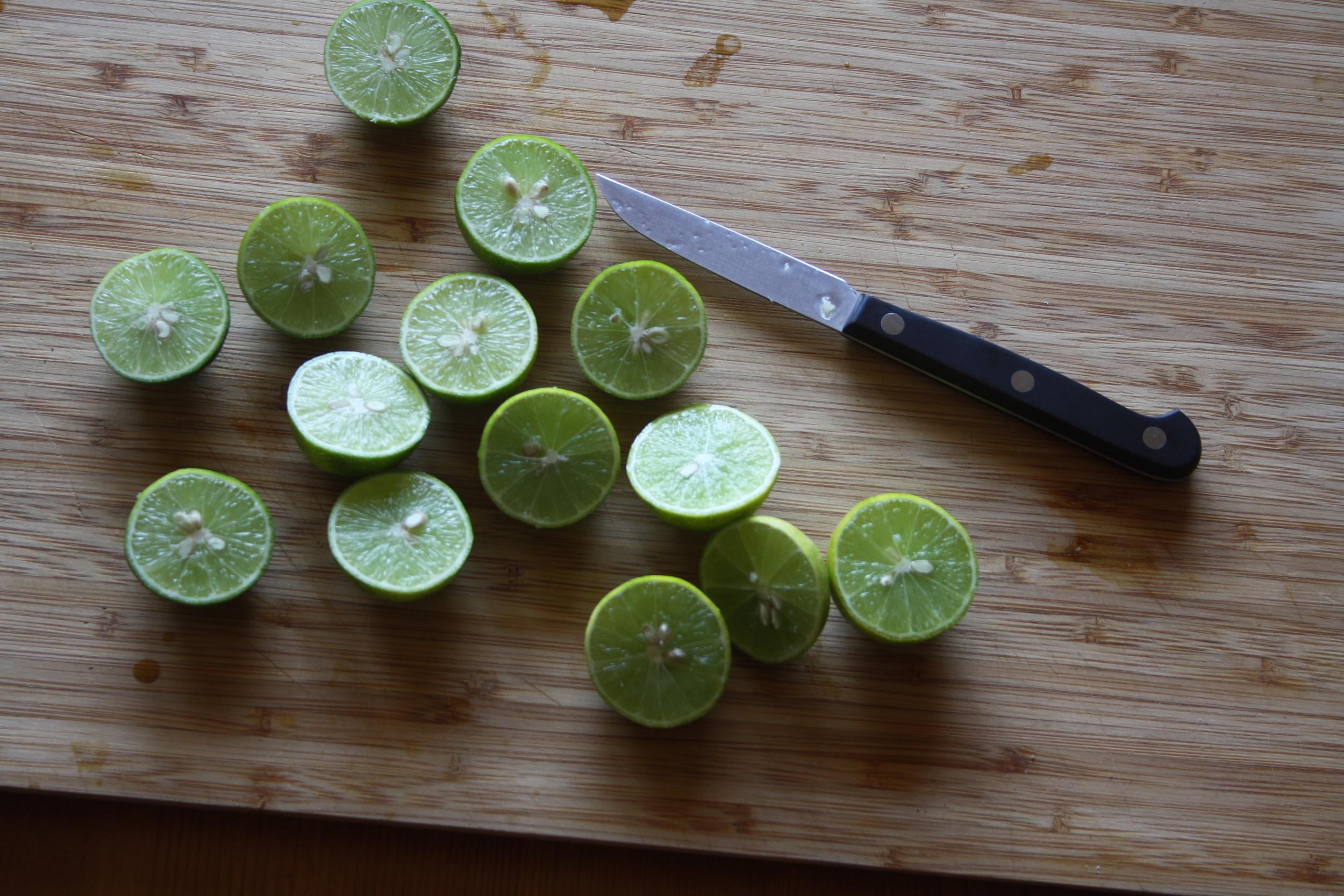 Key Limes sliced on a wooden cutting board