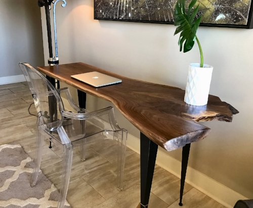 """This live edge black walnut desk will make a simple addition to almost any space. This piece would be well suited as a laptop/computer desk, writing desk, or could be used as a large console/foyer table. The one piece 2"""" thick slab is 18"""" – 28"""" deep, 62"""" wide, and 30"""" tall, and rests on 3"""" tapered angle iron legs..$795.00"""