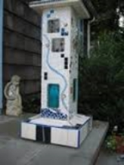 """The """"illumination pillar,"""" fabricated of porcelain tiles, art glass, bisque masks and bits of jewelry by Stephen Albright and presented to his wife, Caroline, in  Finding christmasville."""