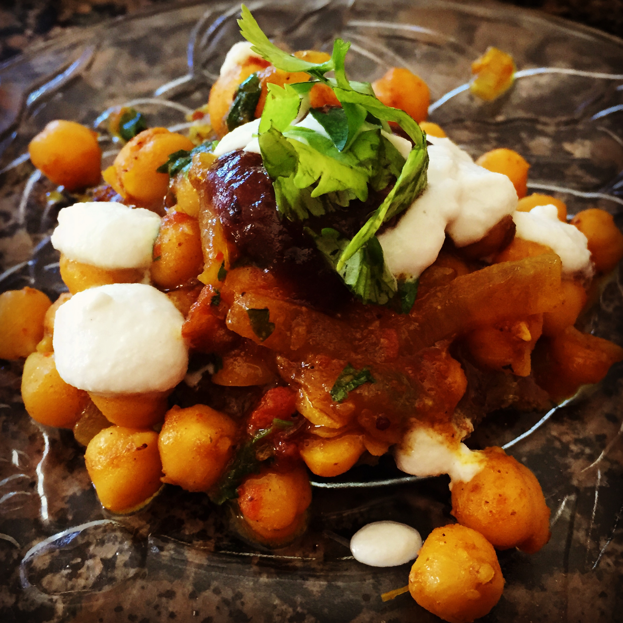 "Our appetizer at the ""Spice of Life"" cooking retreat- Aloo Tikki Chole. Sweet potato quinoa patties topped with spiced chickpeas, tamarind paste, a few dollops of raw cashew cream, and sprinkled with cilantro."