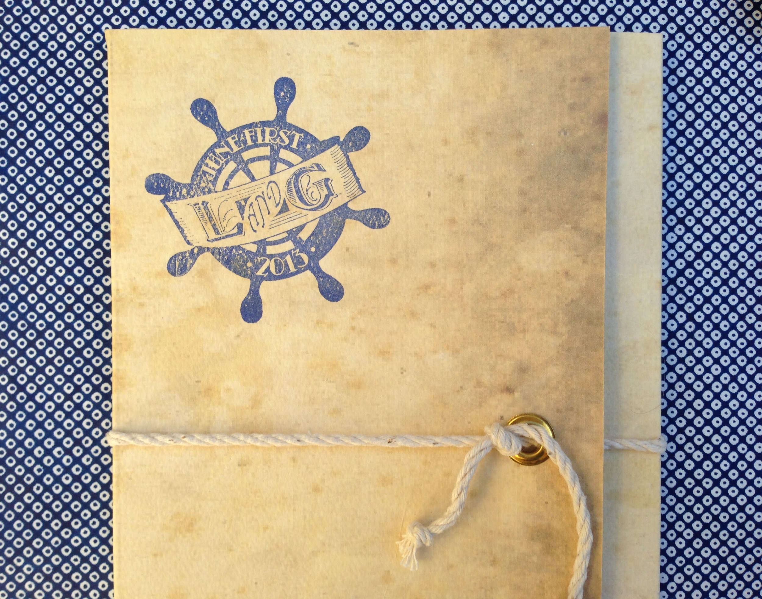 The outside of the folder was fitted with a brass grommet and tied with rope, then stamped with the couple's ship wheel logo.
