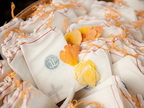 Tiny programs were nestled inside muslin sacks stamped with the couple's logo along side rose petals which were tossed as the newly married couple walked back down the aisle.