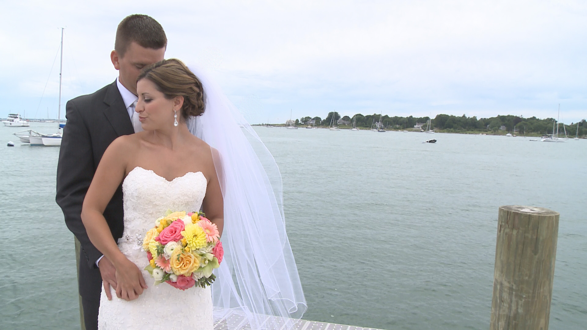 Bride and Groom pose for their photographer after their first look on a dock overlooking Long Island Sound in New London, Connecticut. Wedding Video Connecticut.