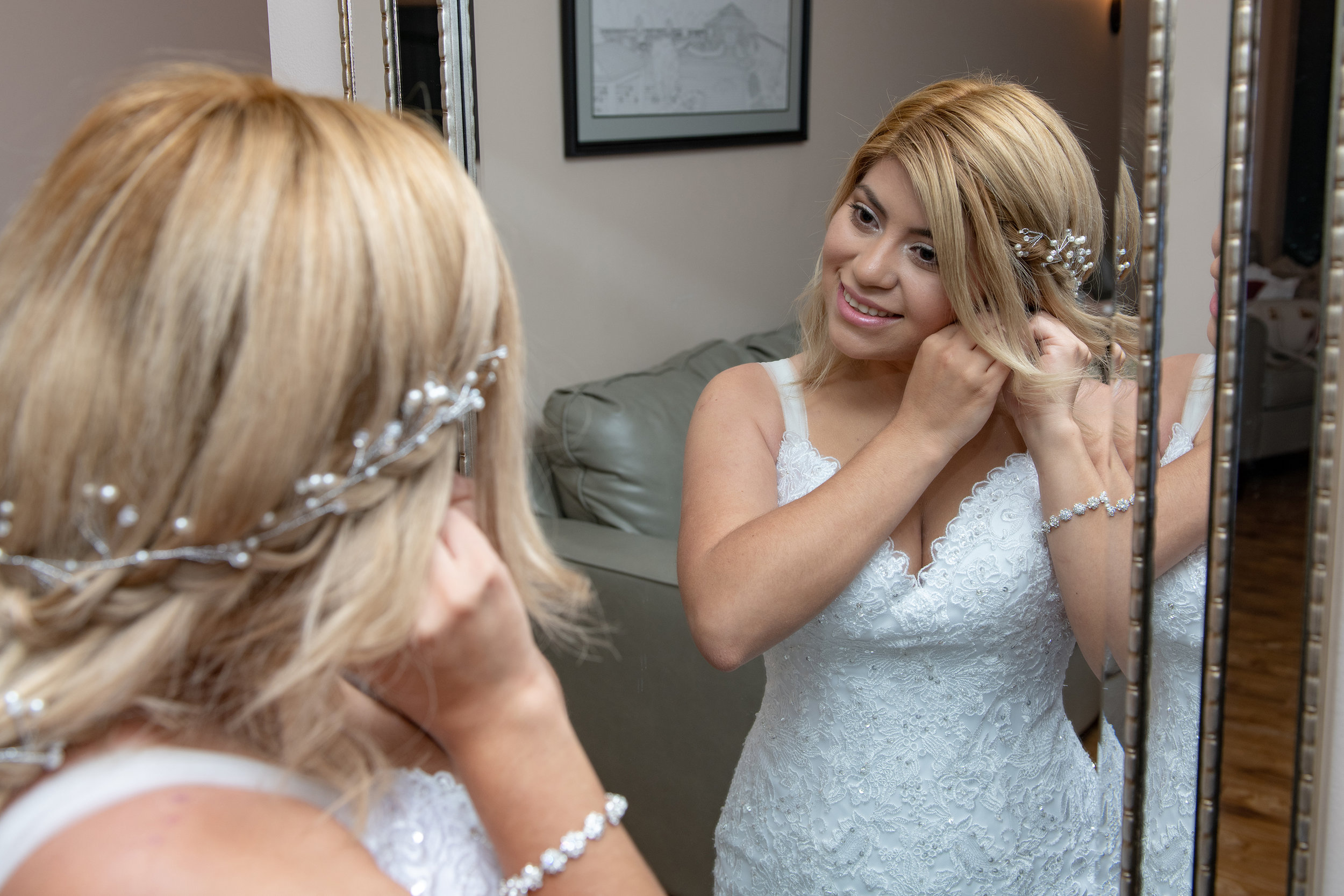 BRIDE PUTTING ON HER EARINGS BEFORE HER WEDDING IN THE BRIDAL SUITE OF THE EMERALD ROOM AT WICKHAM PARK