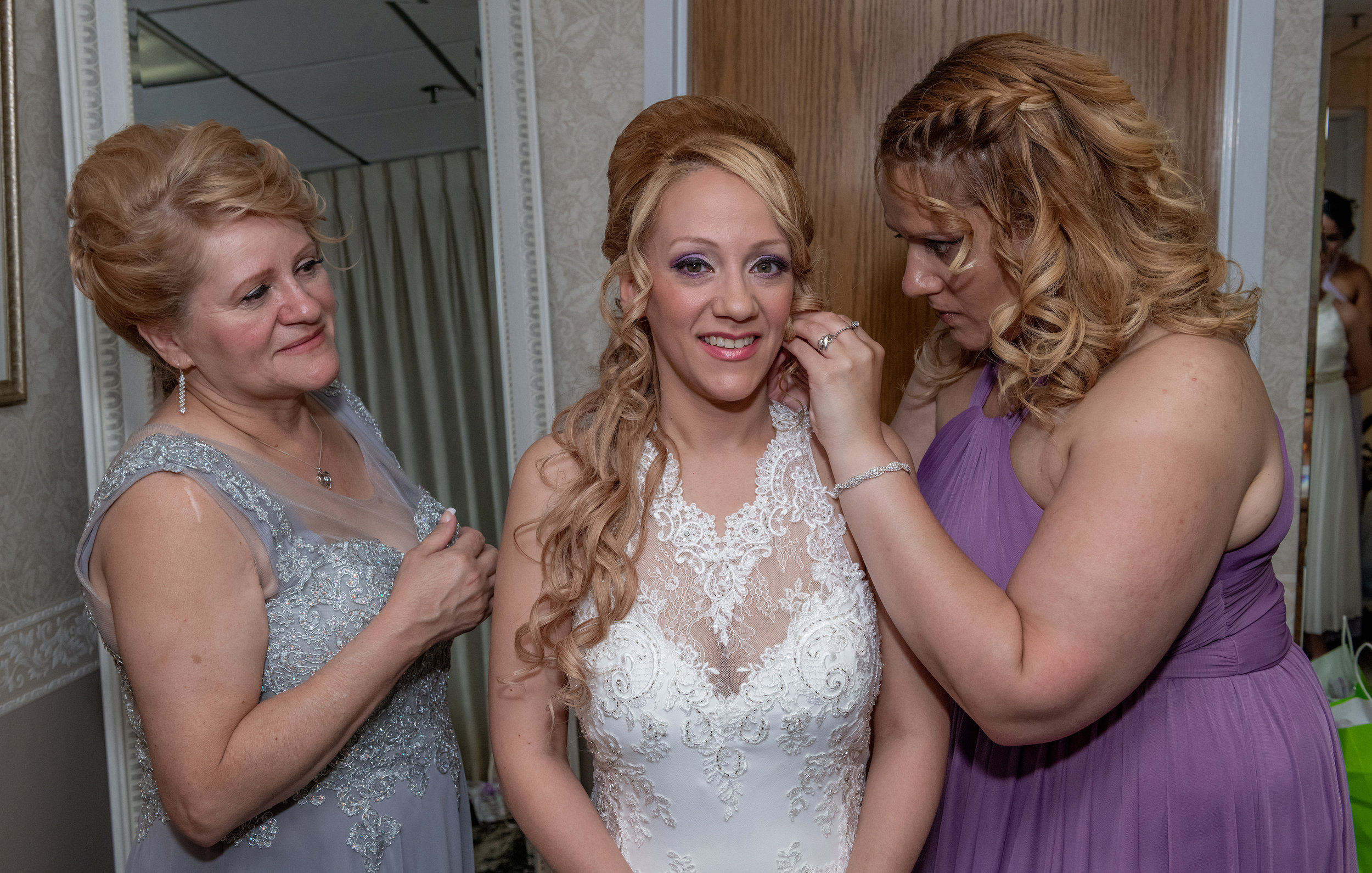 MAID OF HONOR PUTTING EARINGS ON BRIDE.jpg