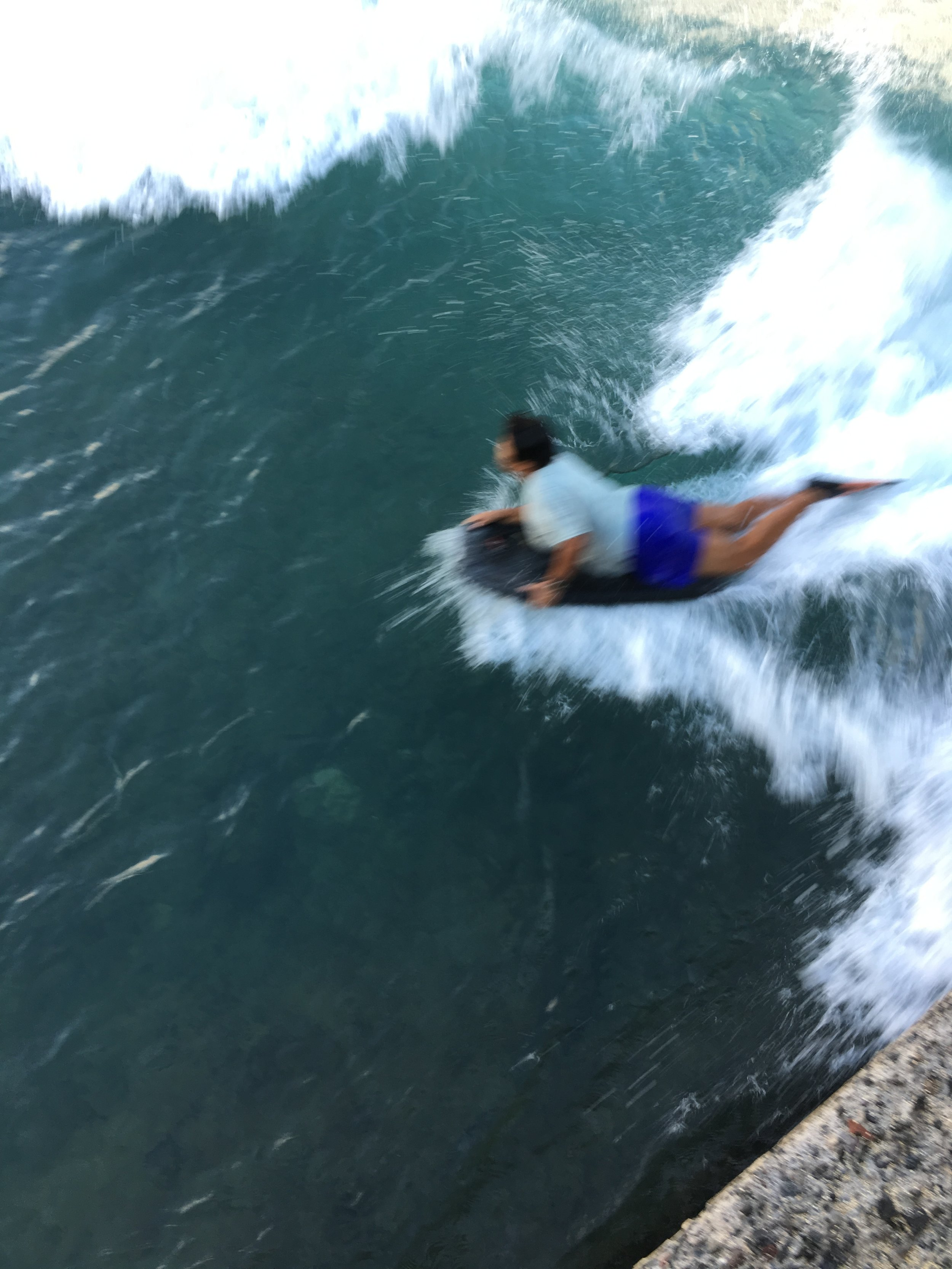 Keiki (kid) riding his boogie board along the Diamond Head side of Walls.