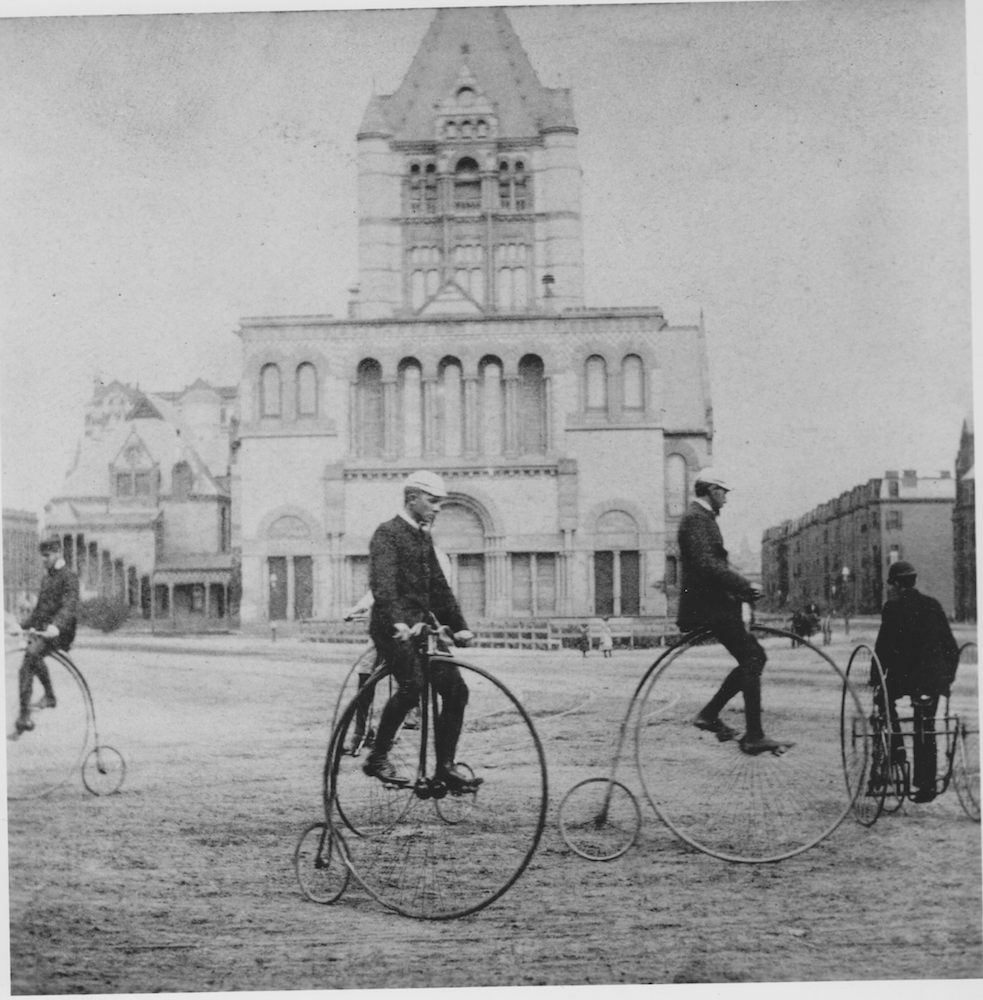 """High-wheel or """"ordinary"""" riders, along with a tricyclist, take a turn around Copley Square in Boston, Massachusetts, about 1880. National Archives RG 306 PS D (61–10196)."""