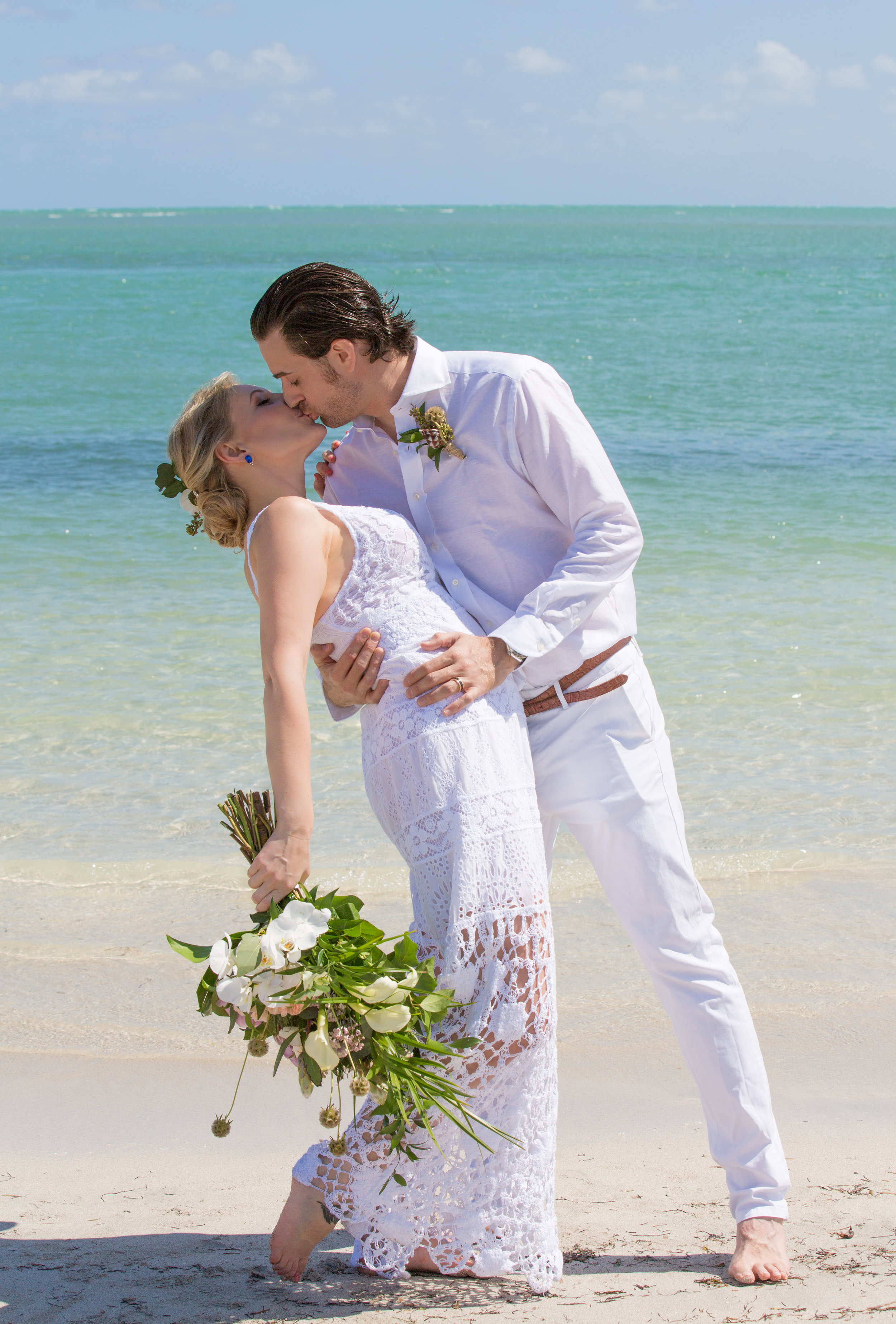 Groom and bride kiss at simple wedding on Key Biscayne. She is holding her tropical bride bouquet and he is wearing a vintage grooms boutonniere