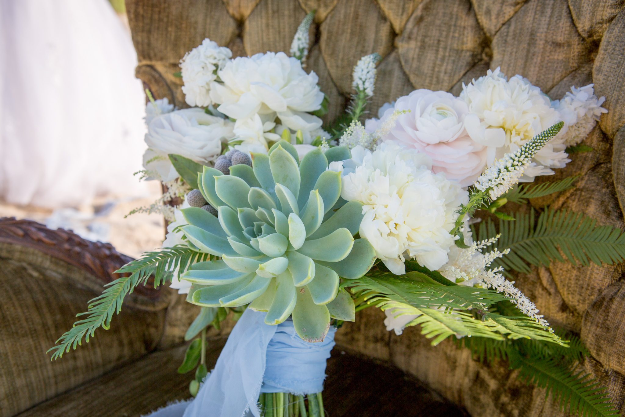 Natural bride bouquet with succulent sits on plush leather chair on Miami Beach