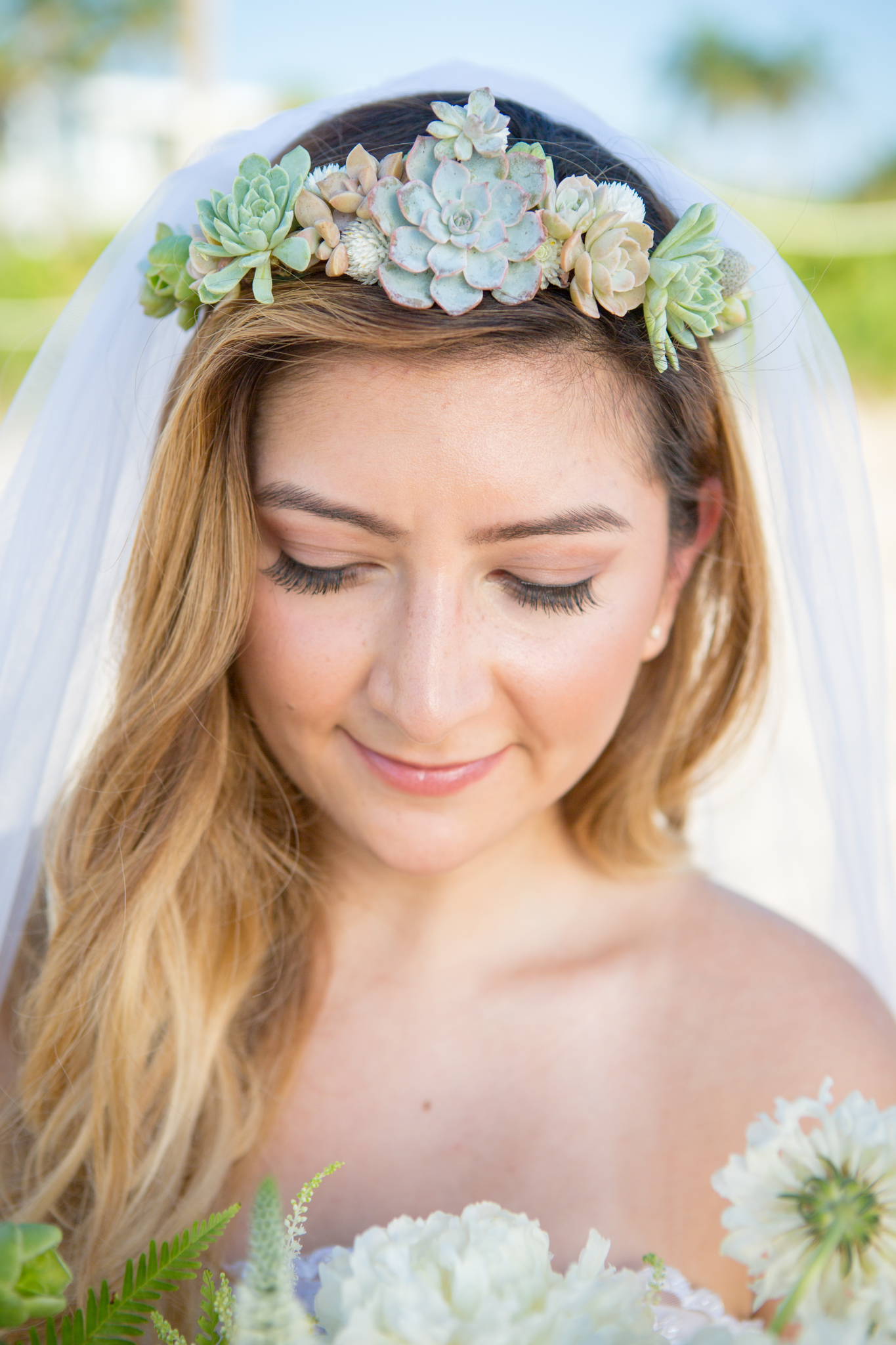 Close-up of bride's flower crown made of succulents at beach wedding