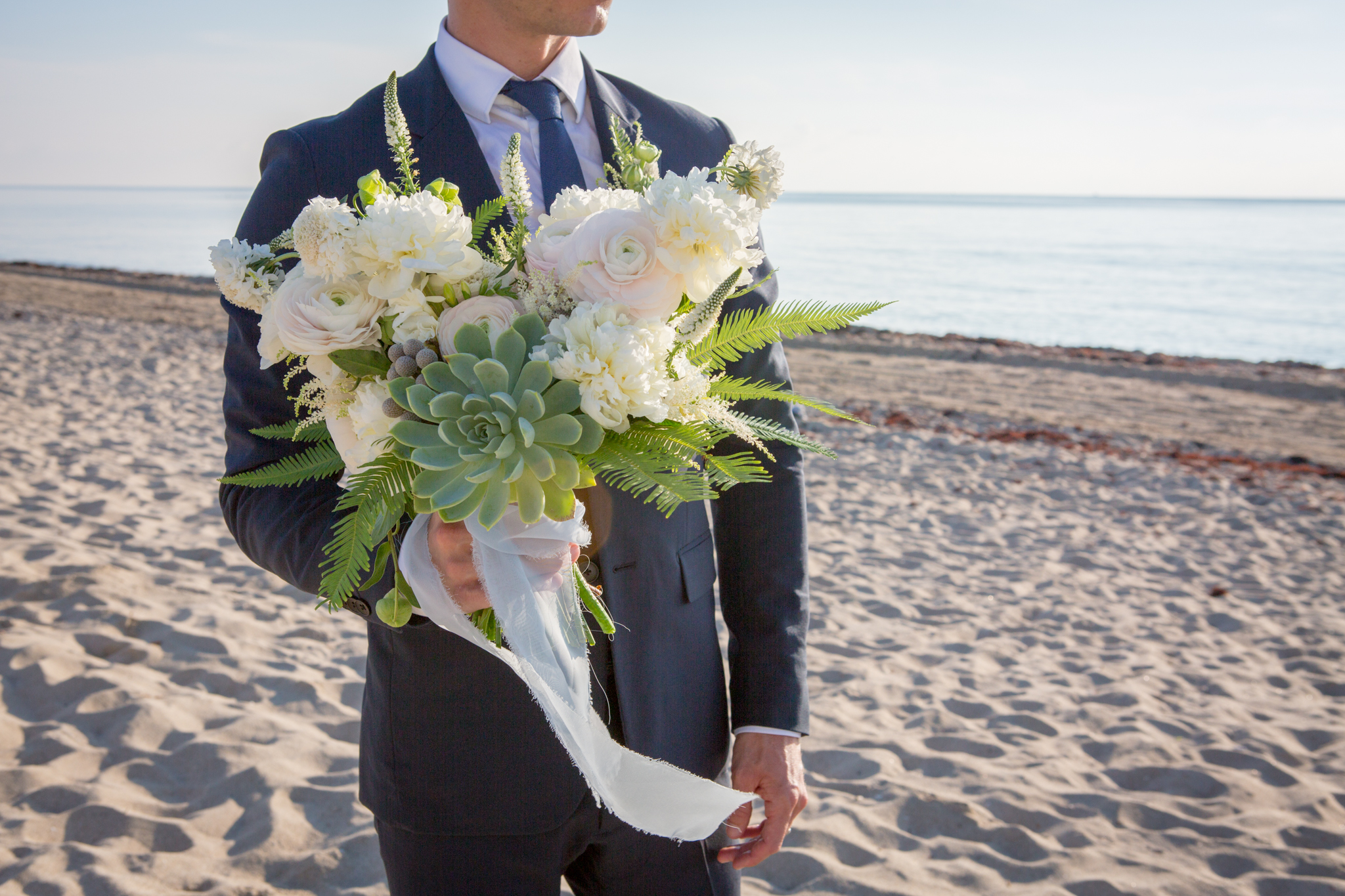 Groom on beach holding natural bride bouquet