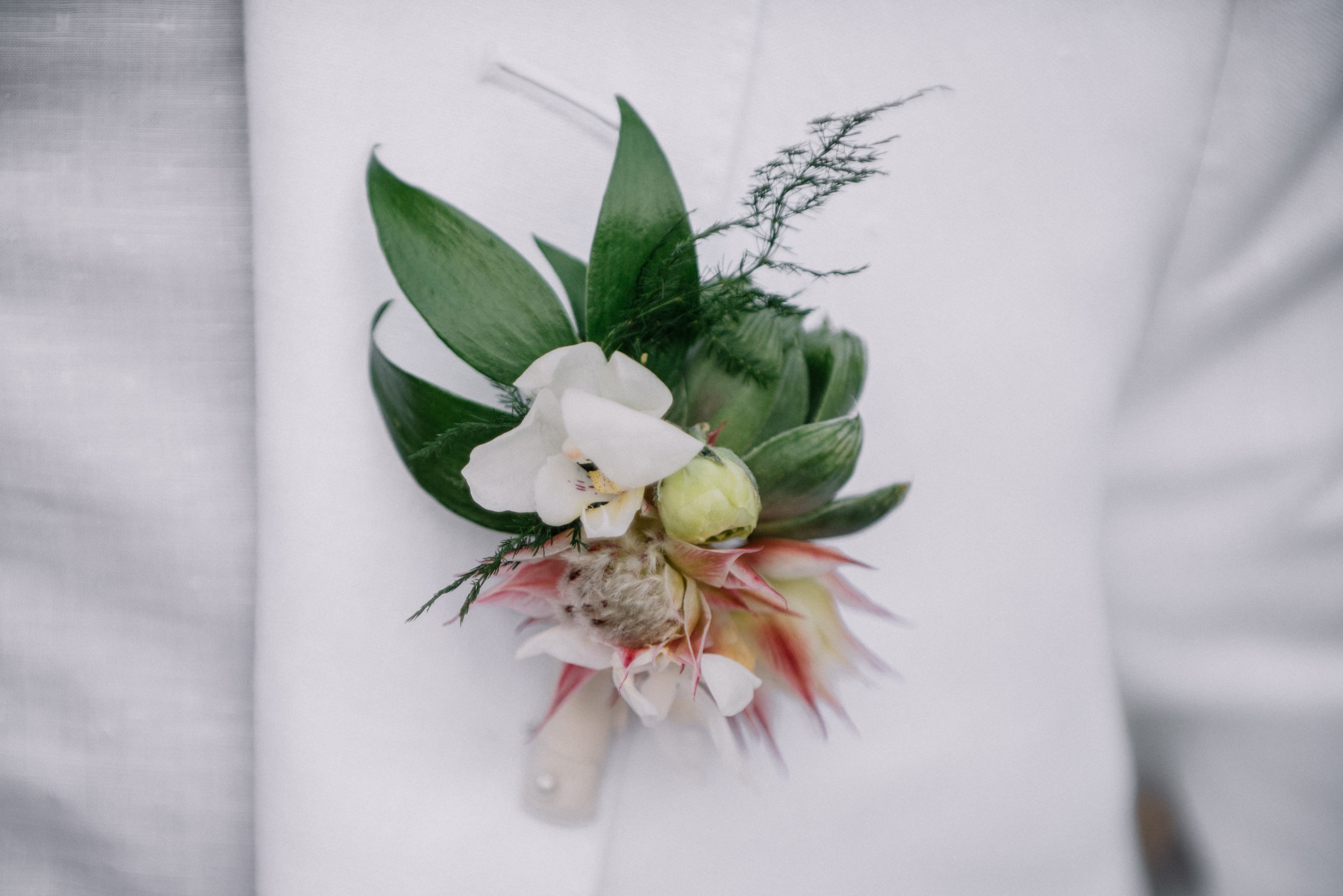 Grooms boutonnière with wedding flowers at  Deering Estate  in Miami