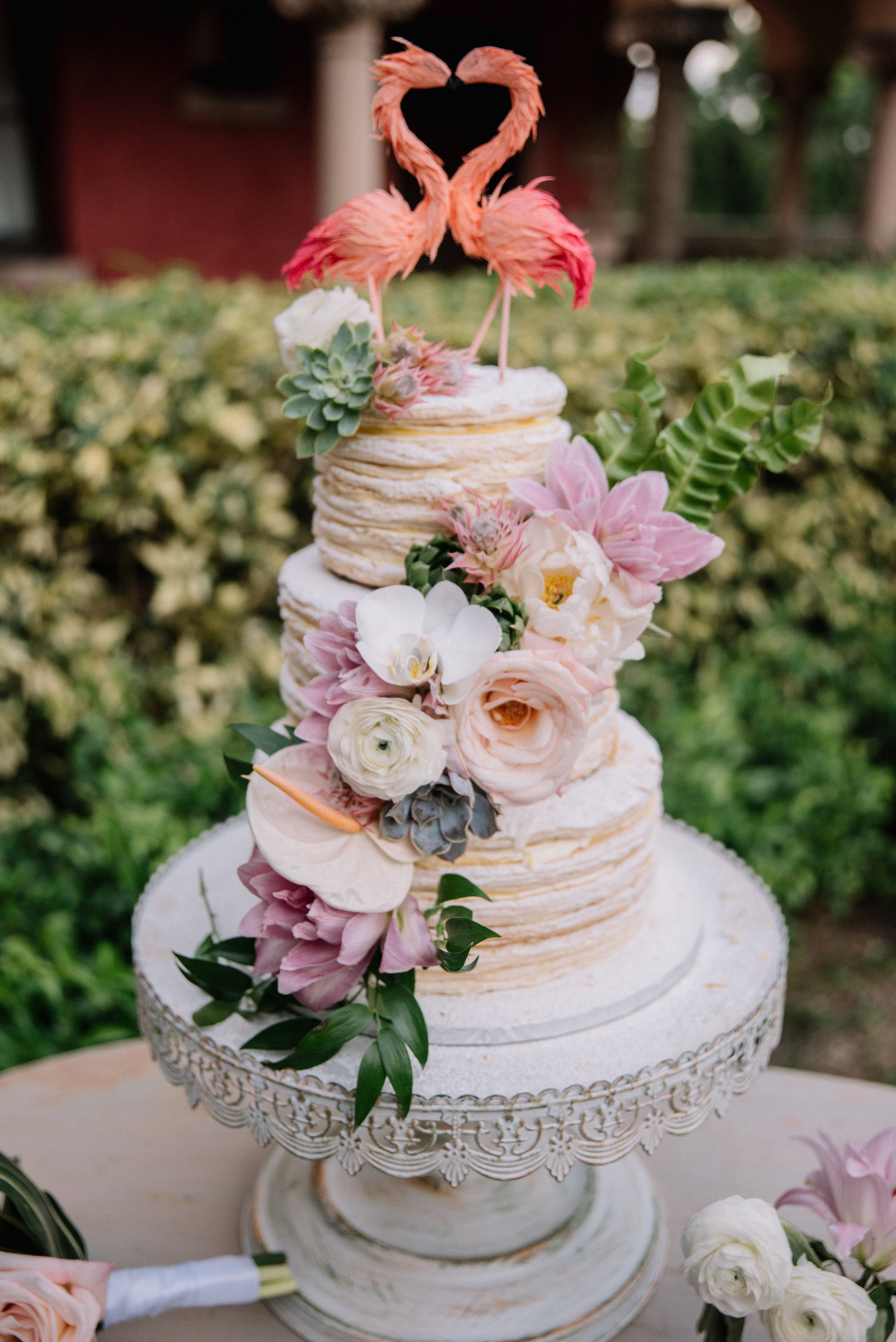 Cascading tropical wedding cake flowers in blush and white on naked cake with pink flamingo topper at  Deering Estate  in Miami