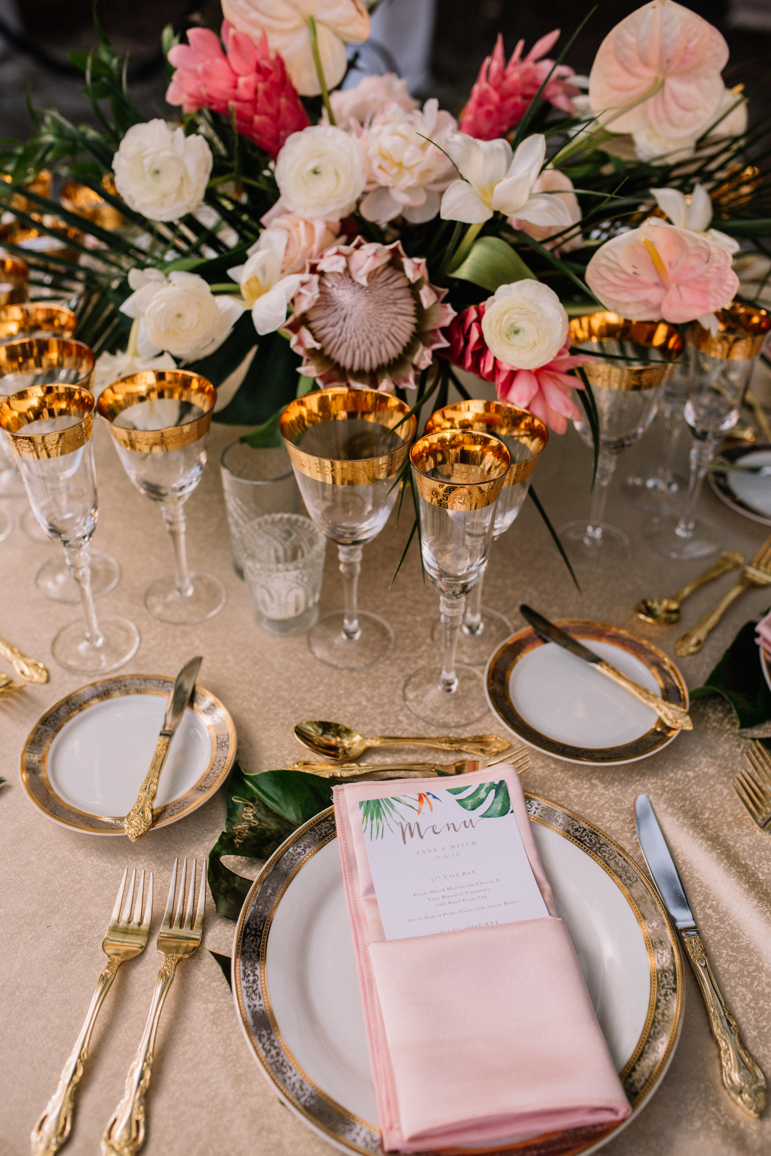 Tropical Miami centerpiece on tablescape with golden goblets, flatware, and china at Miami  Deering Estate
