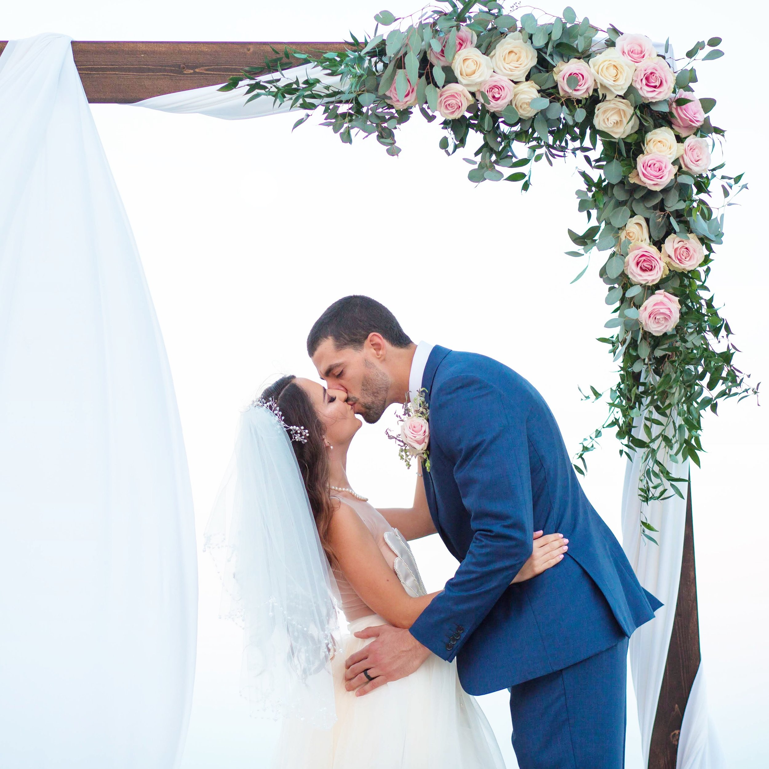 Whimsical wedding arch with lush flowers and greenery on the beach at Miami Beach