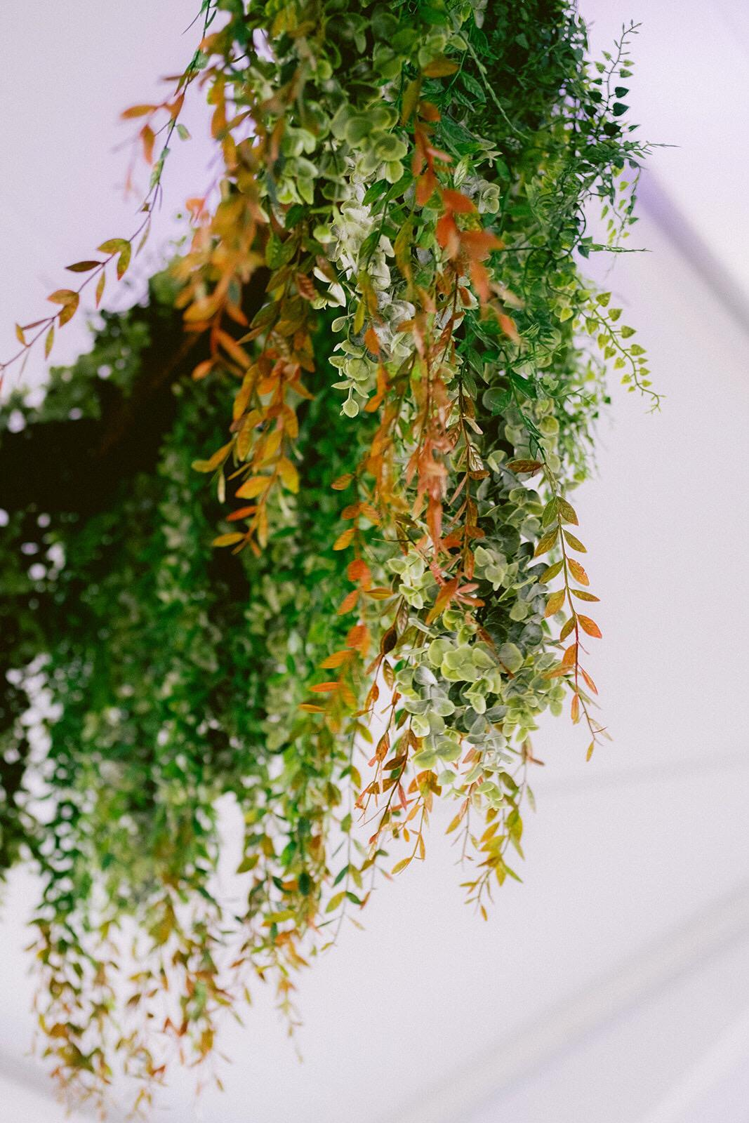 Greenery hangs from a floral chandelier at at wedding at  Vizcaya  in Miami