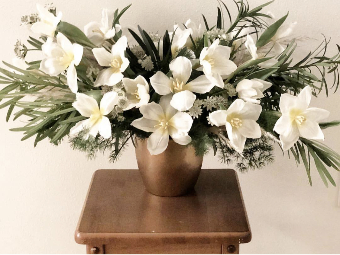 Floral centerpiece with white tulips and mimosa.