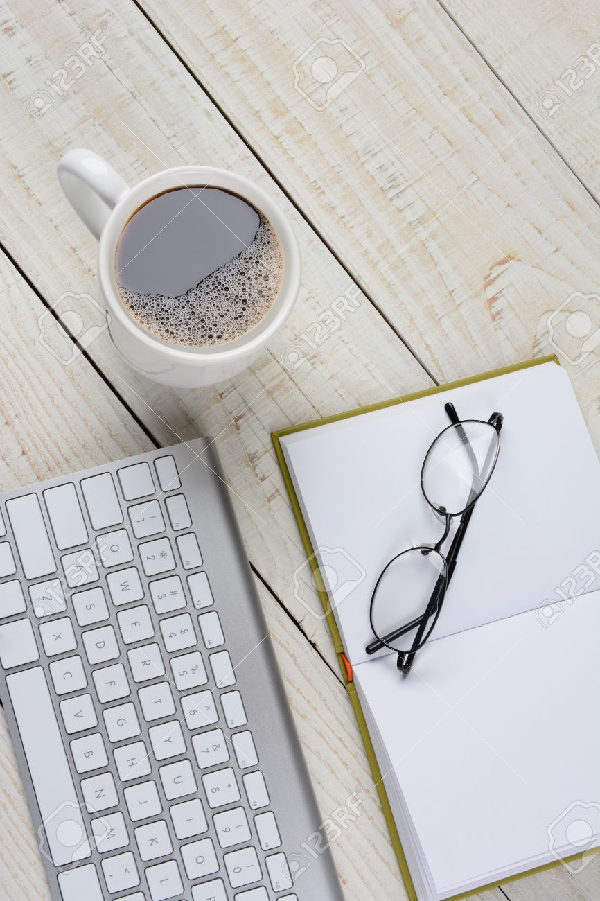 34944576-Vertical-overhead-shot-of-a-home-office-desk-with-a-cup-of-coffee-and-open-book-with-glasses-and-a-c-Stock-Photo.jpg