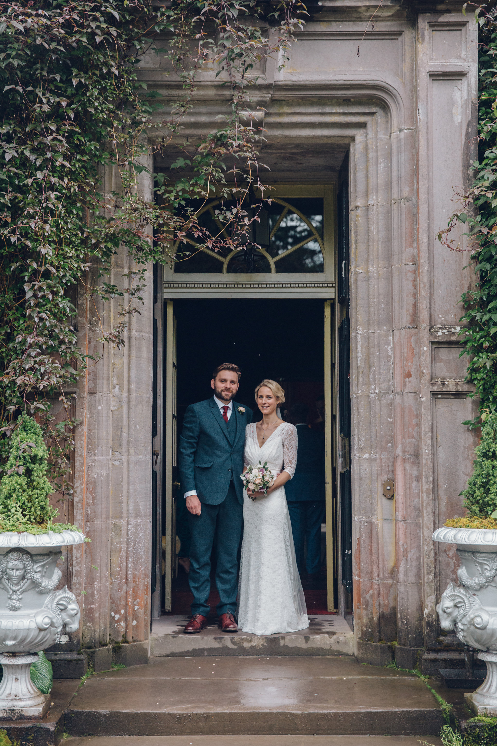 Lovely bride Alisa wears the Halfpenny London Josephine lace wedding dress with cross over front and low V back with three quarter lace sleeves and a blush pink sash worn with a French lace trim veil