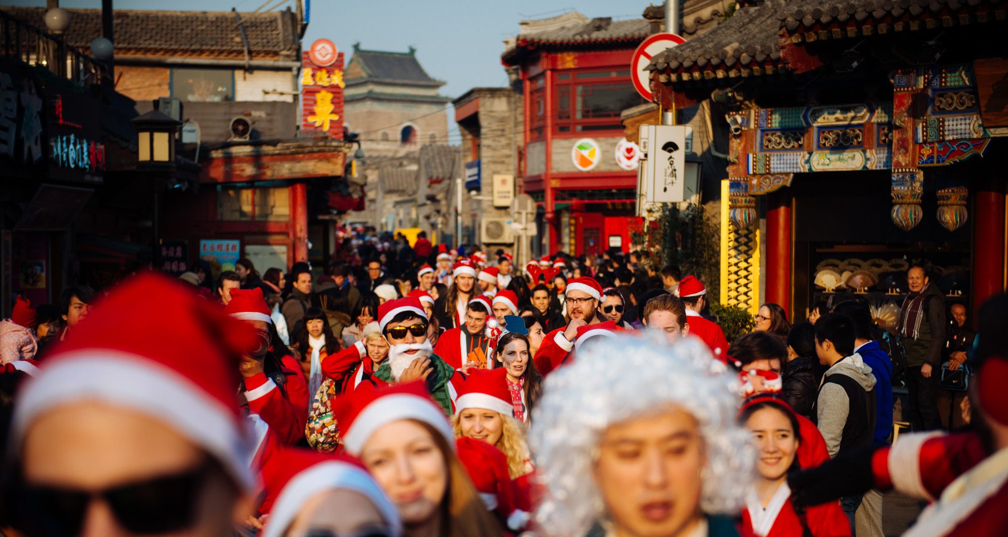 Hundreds of Santas in the historical district of Beijing on the Houhai Lake bridge. In the back you can see the Bell Tower.