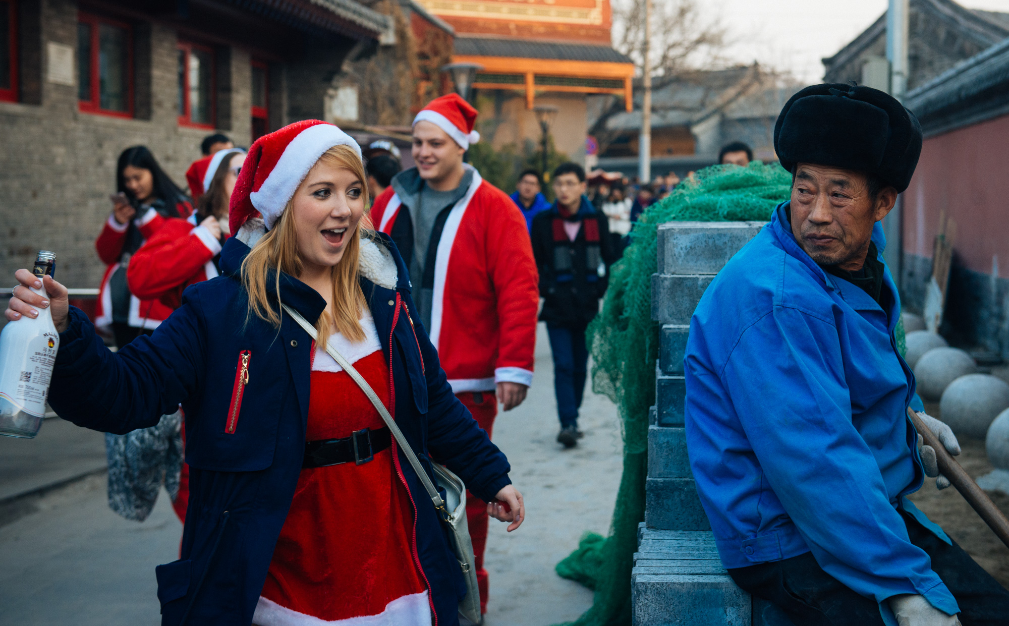 """Santa interacts with a local worker doing renovations that must be thinking """"what are these foreigners doing? Strange group of fellows."""""""