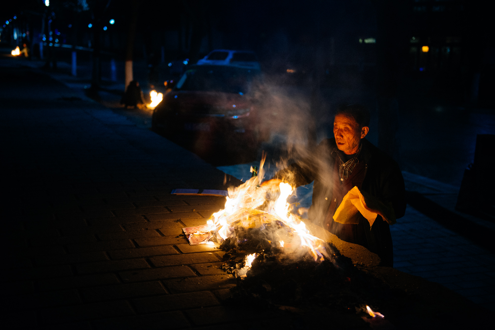 Right at the bottom of the east side of the old city walls, an old man burns tons of paper.