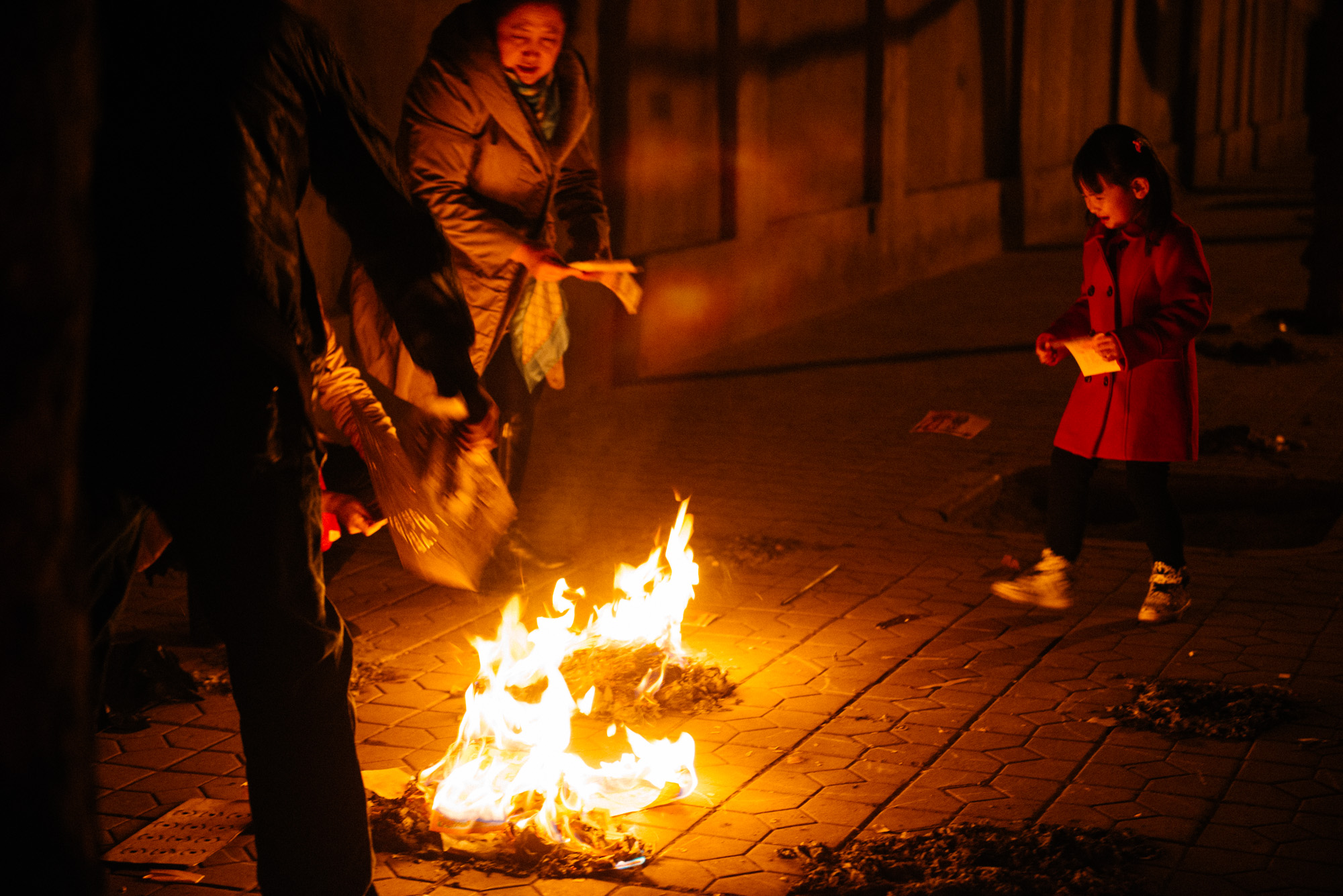 This little girl was very scared of the fire. Her grandmother would tell her to throw the money in but at first she wouldn't. After a few tears, she gathered the courage.