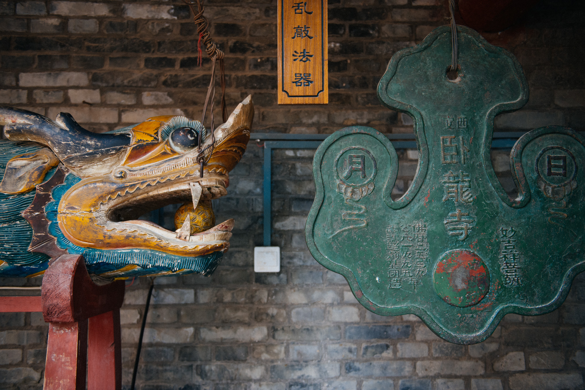 """To the right, a bell-like structure and to the left the thing to bang it with. You can see 卧龙寺 (Wolong Temple) written on the """"bell"""" (I don't know how else to call this)."""