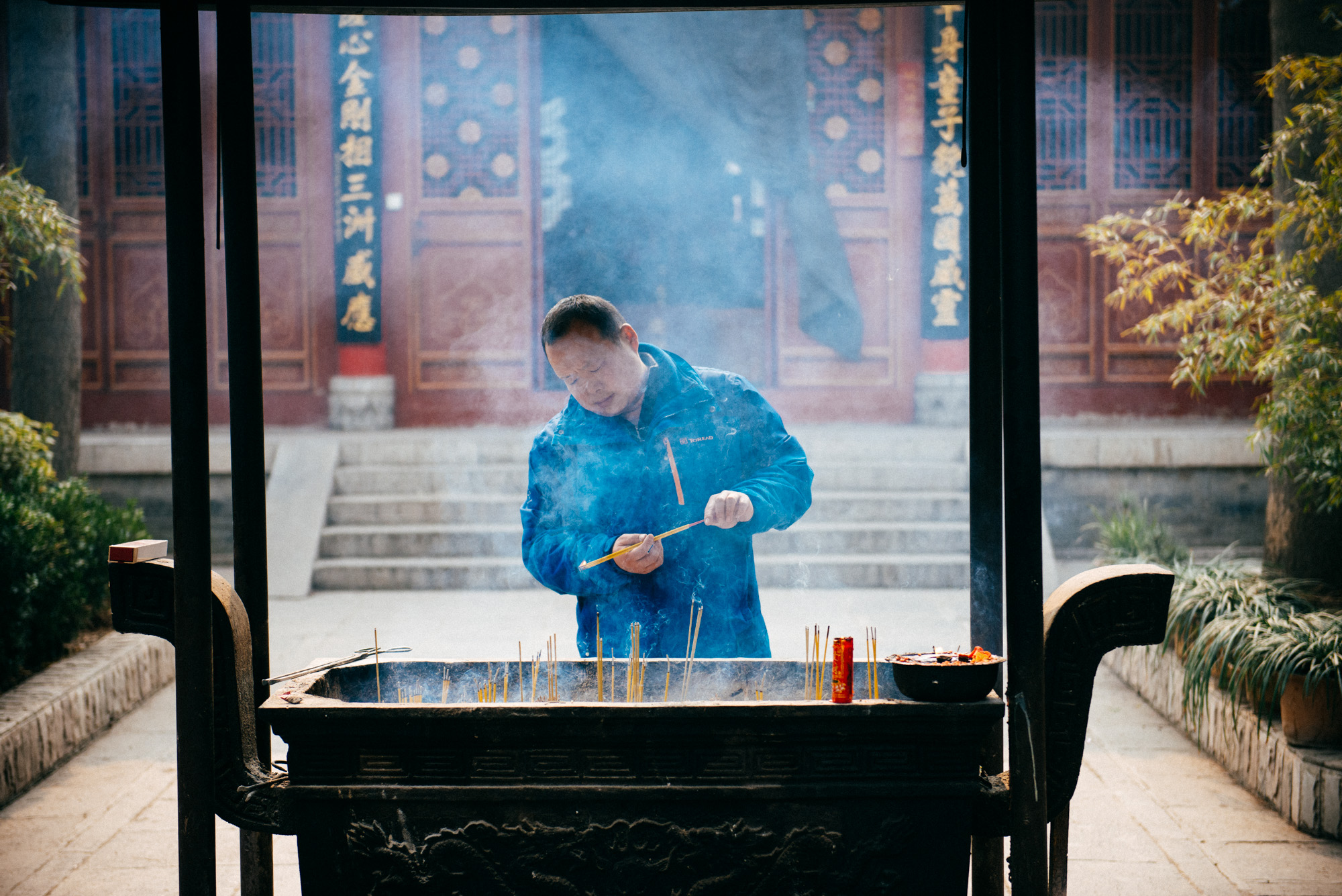 Man lights incense sticks before praying in front of a Buddha statue.