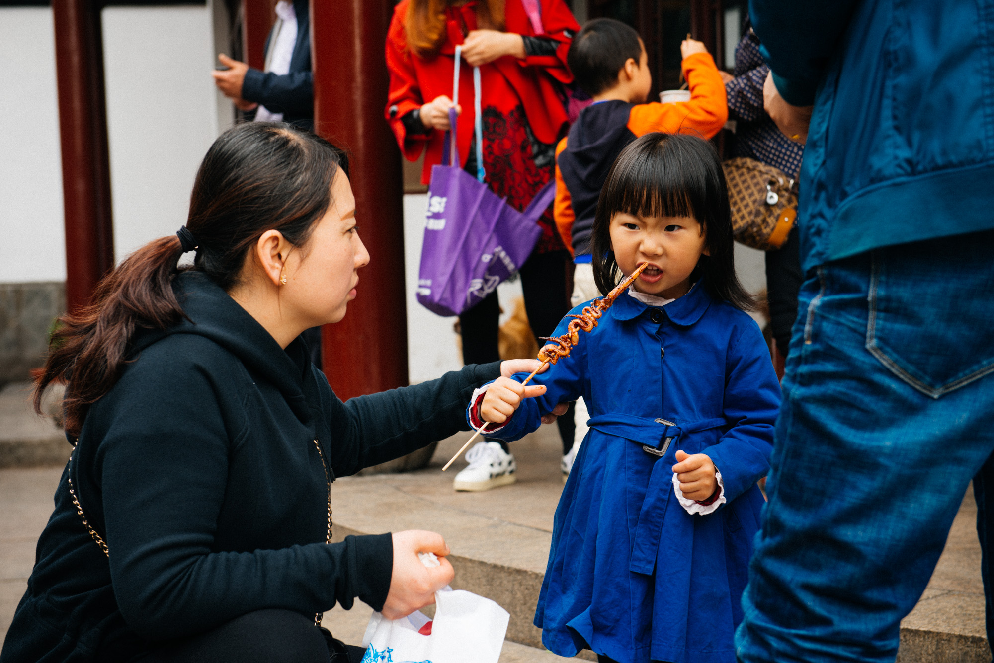 Little girl struggles to eat a squid tentacle. Street food is one of the main attractions in Qibao.