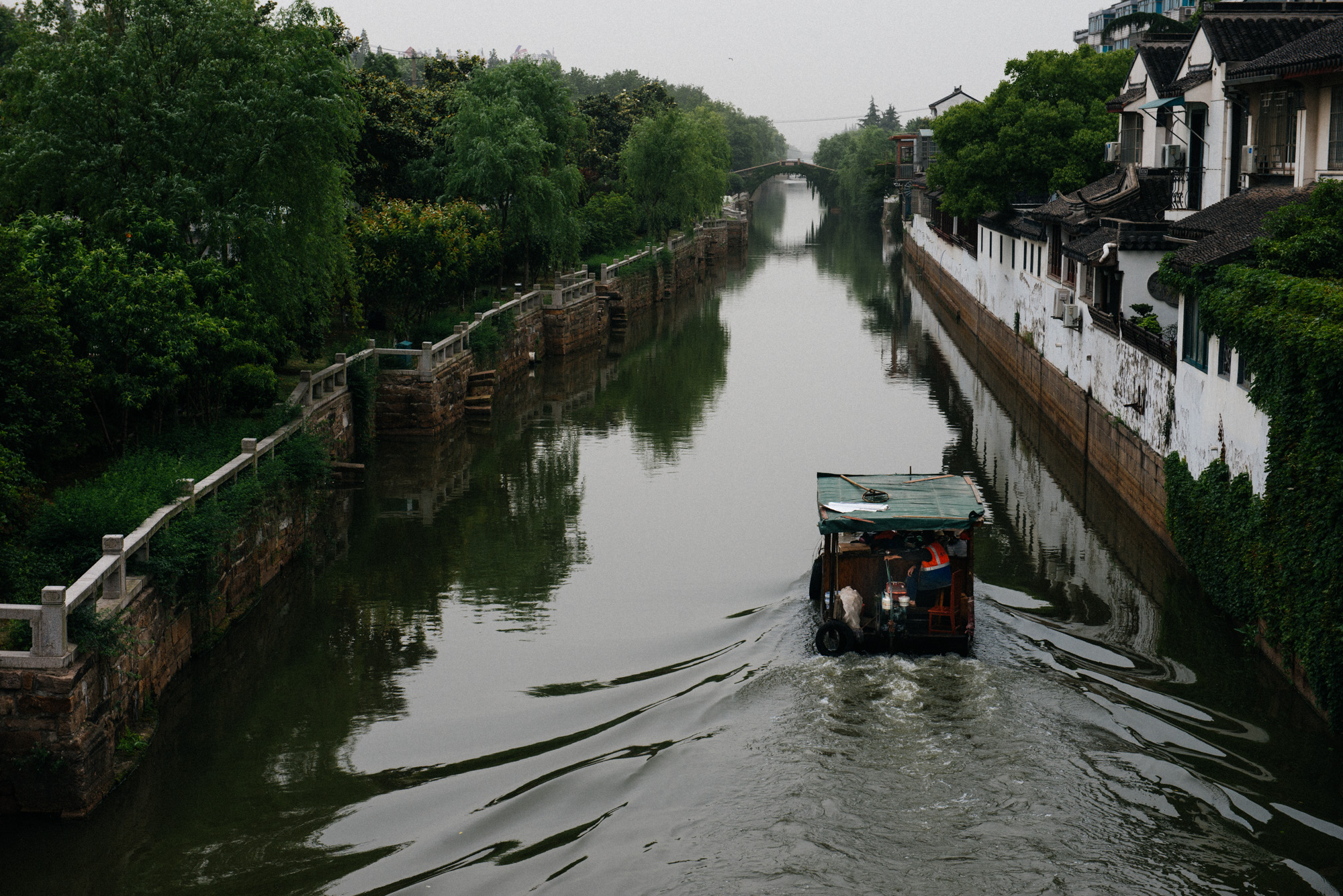 A boat used for cleaning the water passes through a canal close to the  Lingering Garden .