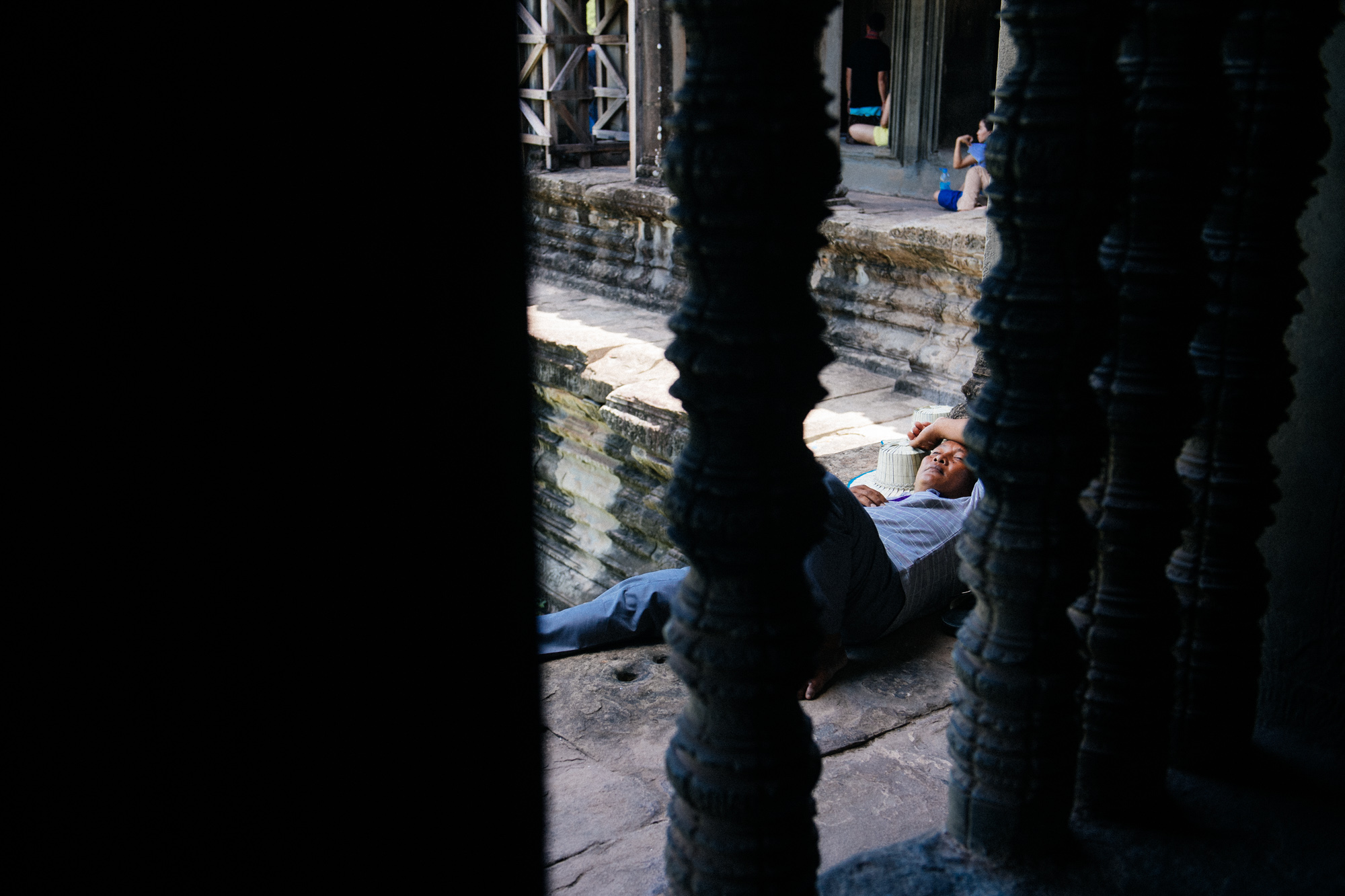 Man takes a break from the hot and humid Cambodian summer outside a window at the Wat.