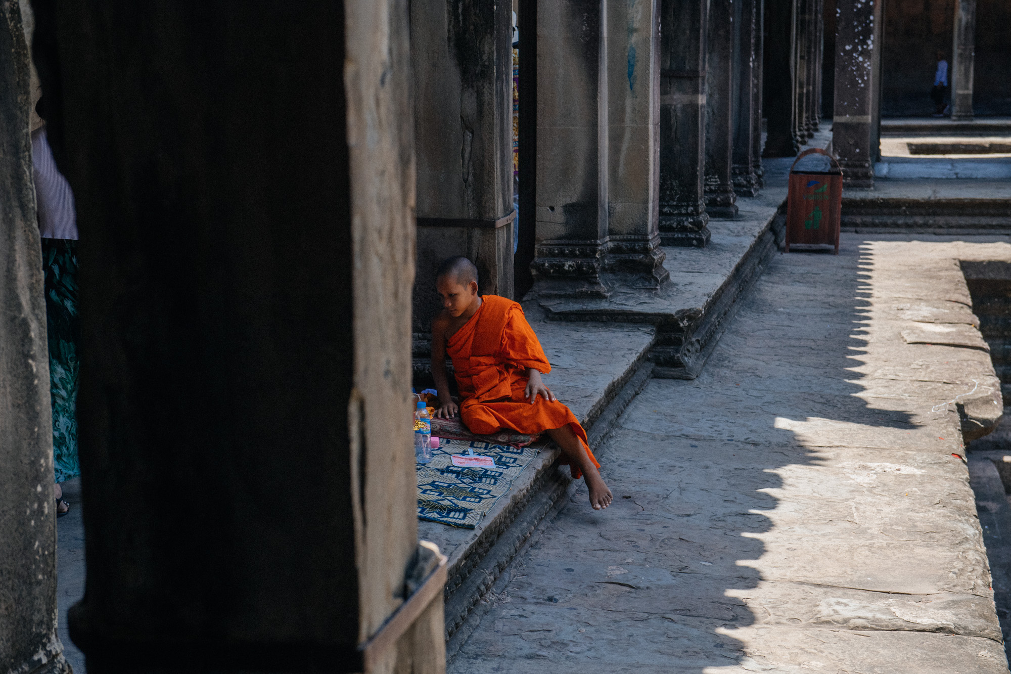 Two young monks rested beside the empty pools at the base of the temple. Many people would stop and donate them money and pray.
